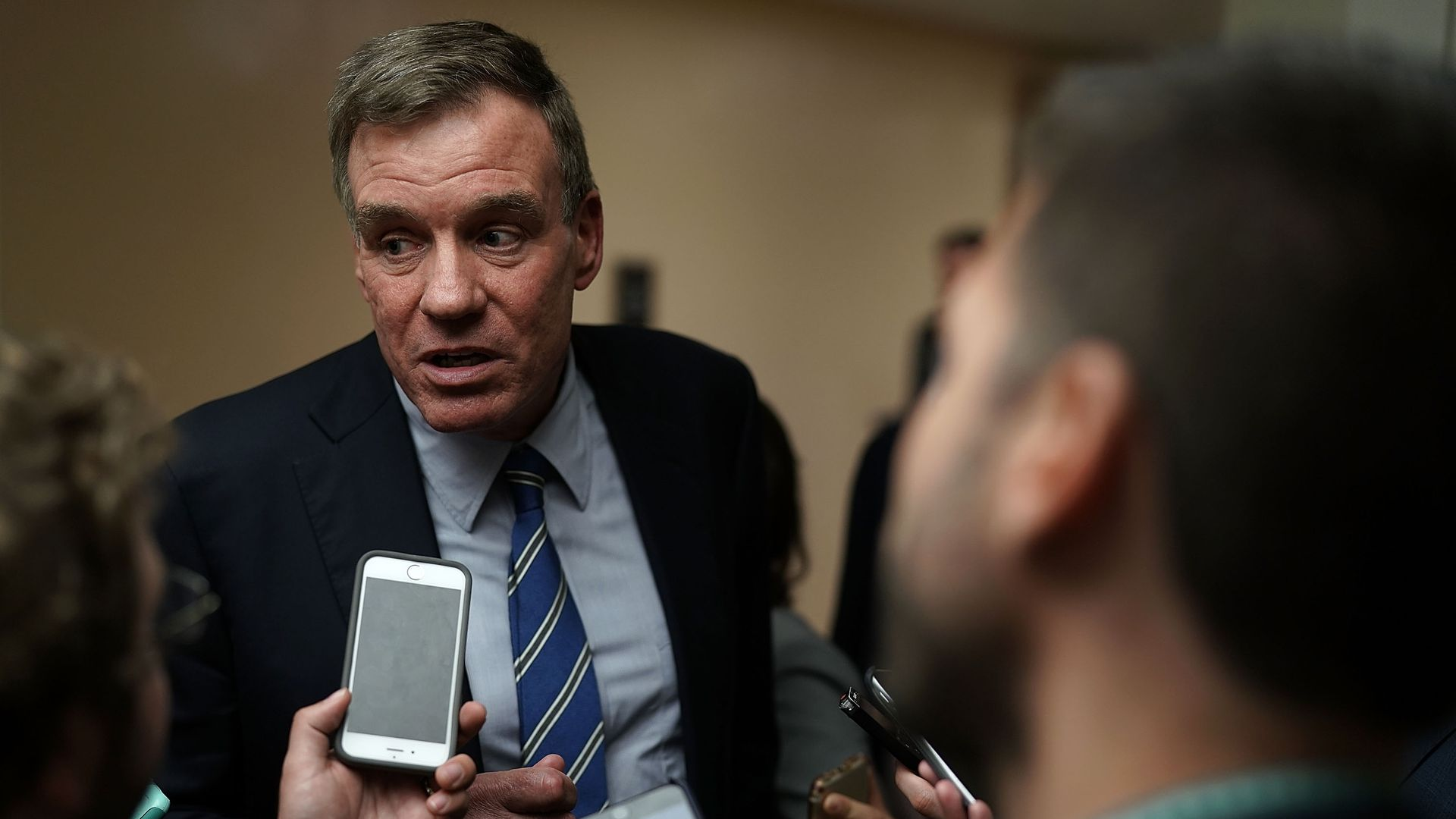 Mark Warner talks to reporters