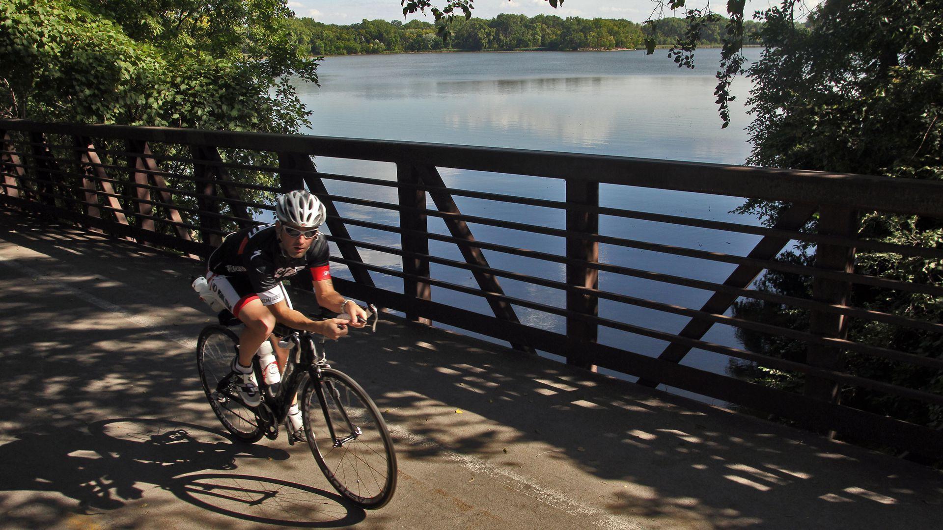 A bicyclist riding across a bridge.