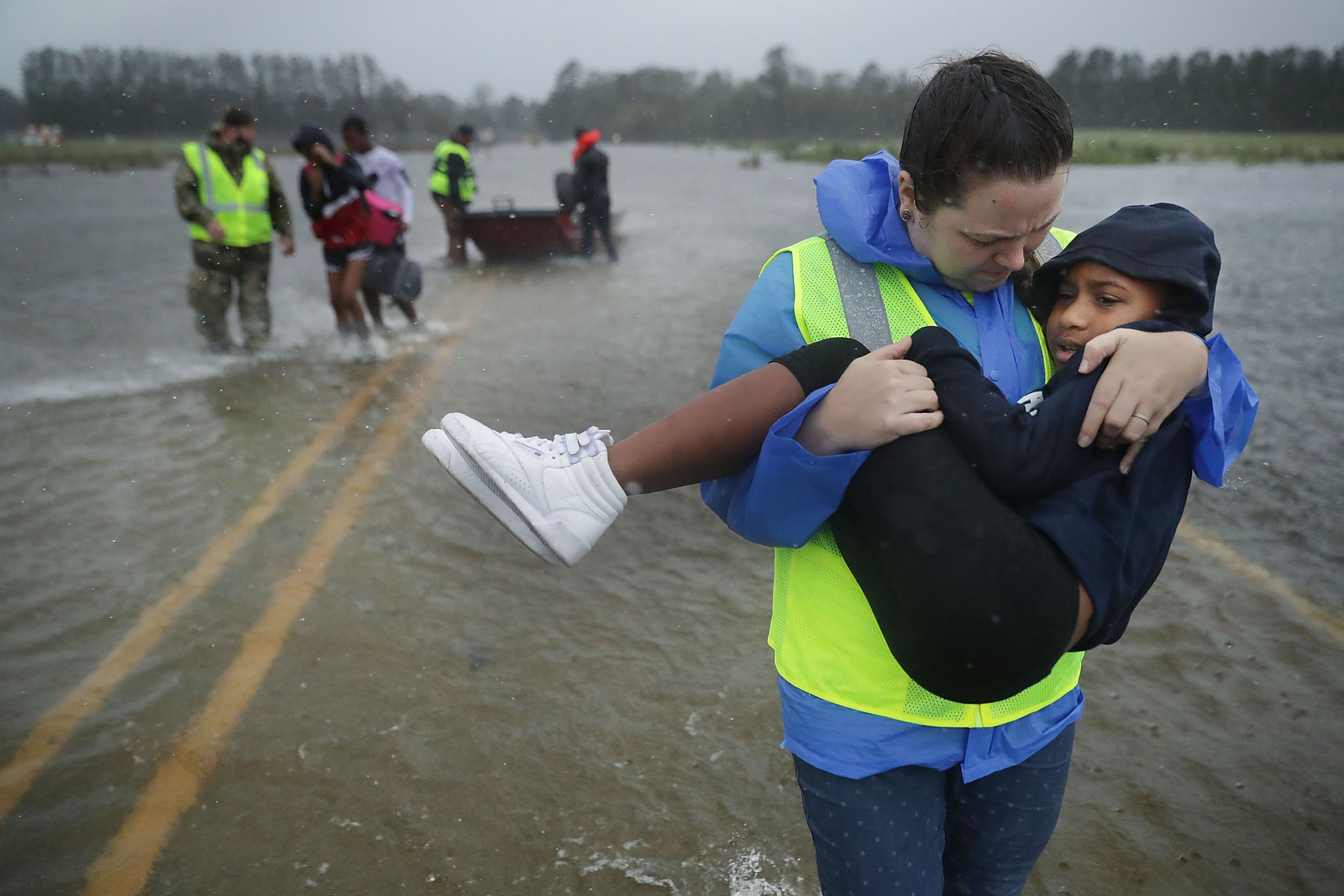 A volunteer carries a child through the water.