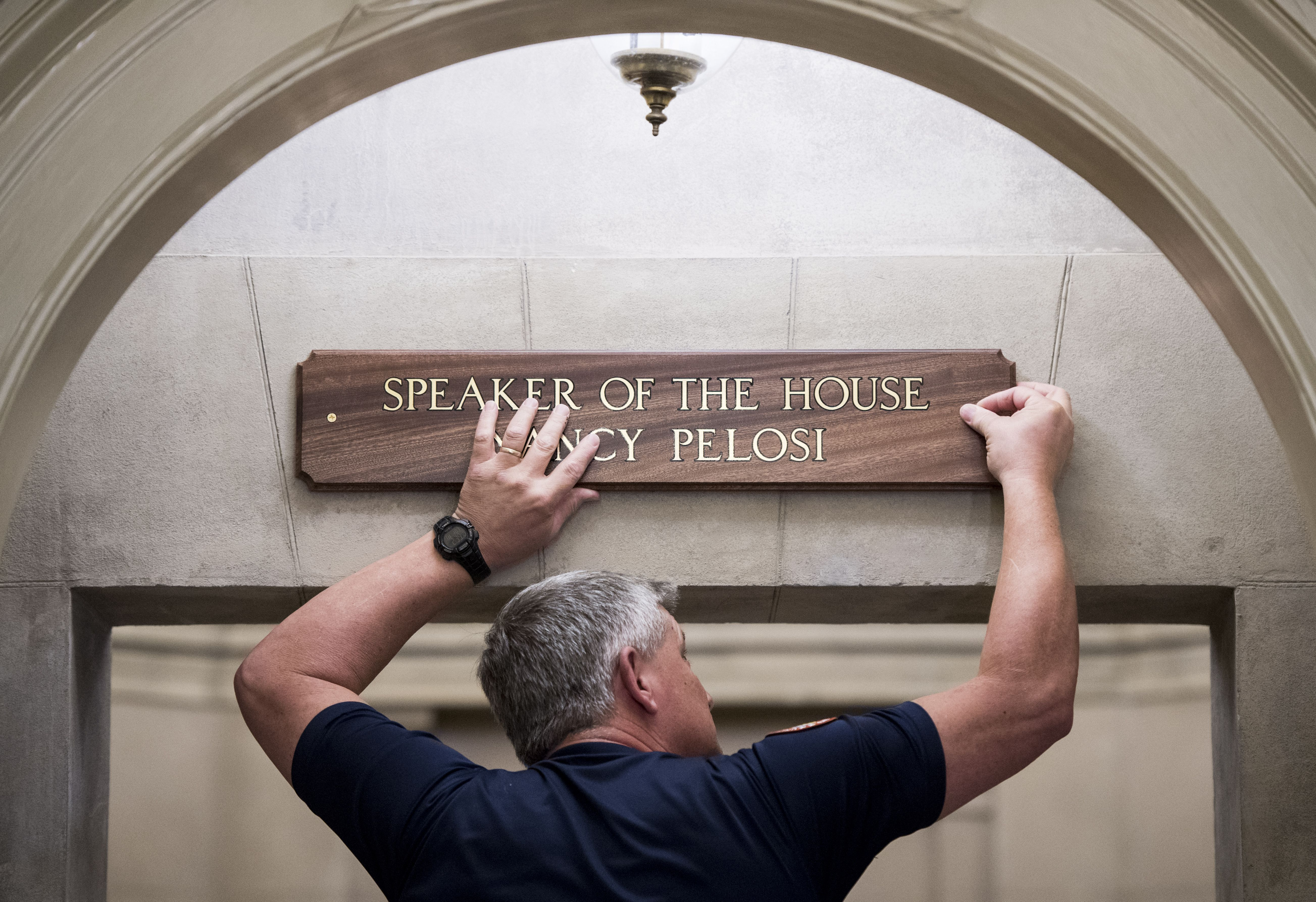 Employee hanging speaker of the house nancy pelosi sign above doorway