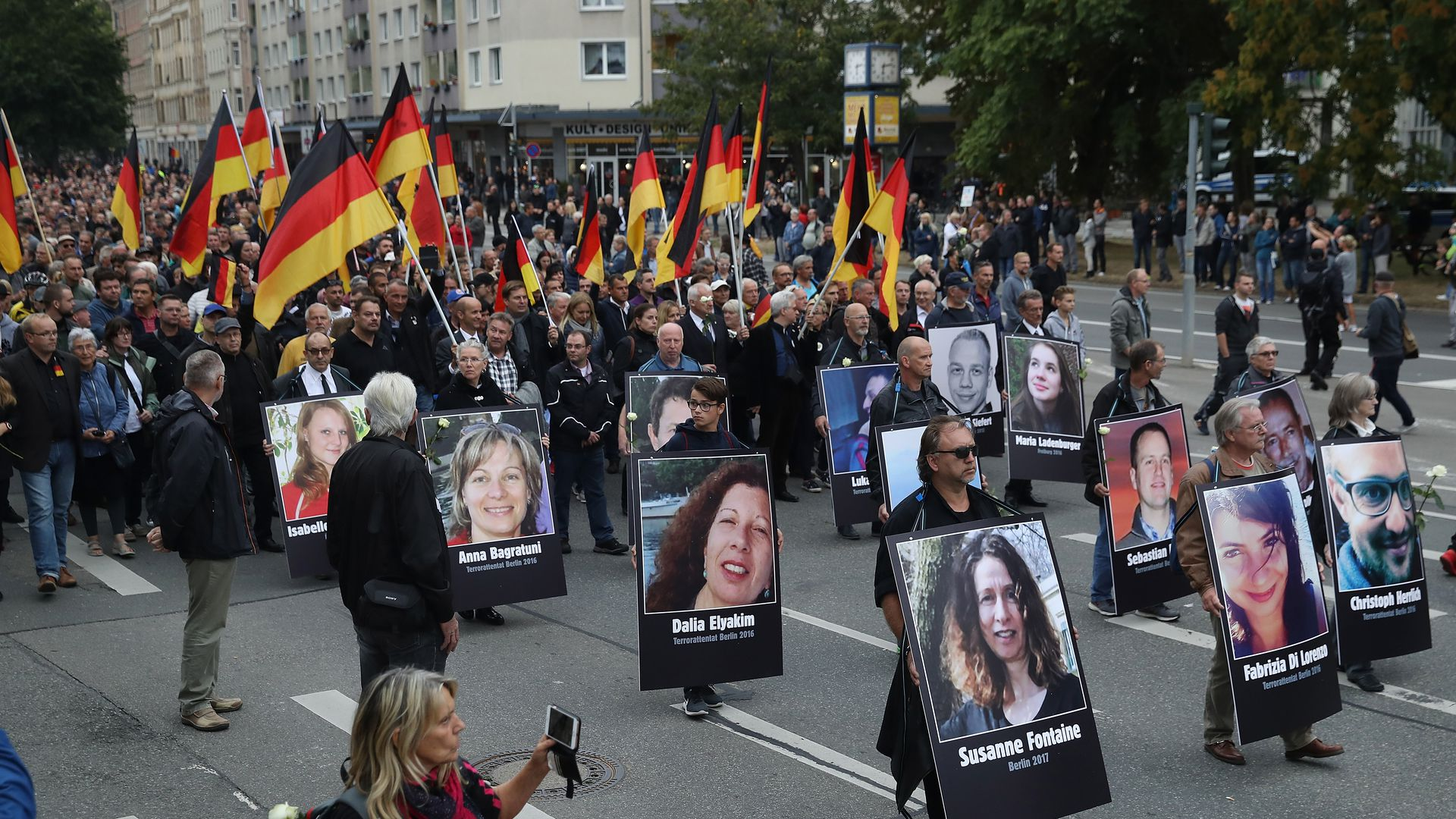Protestors carrying German flags and portraits of people killed by migrants