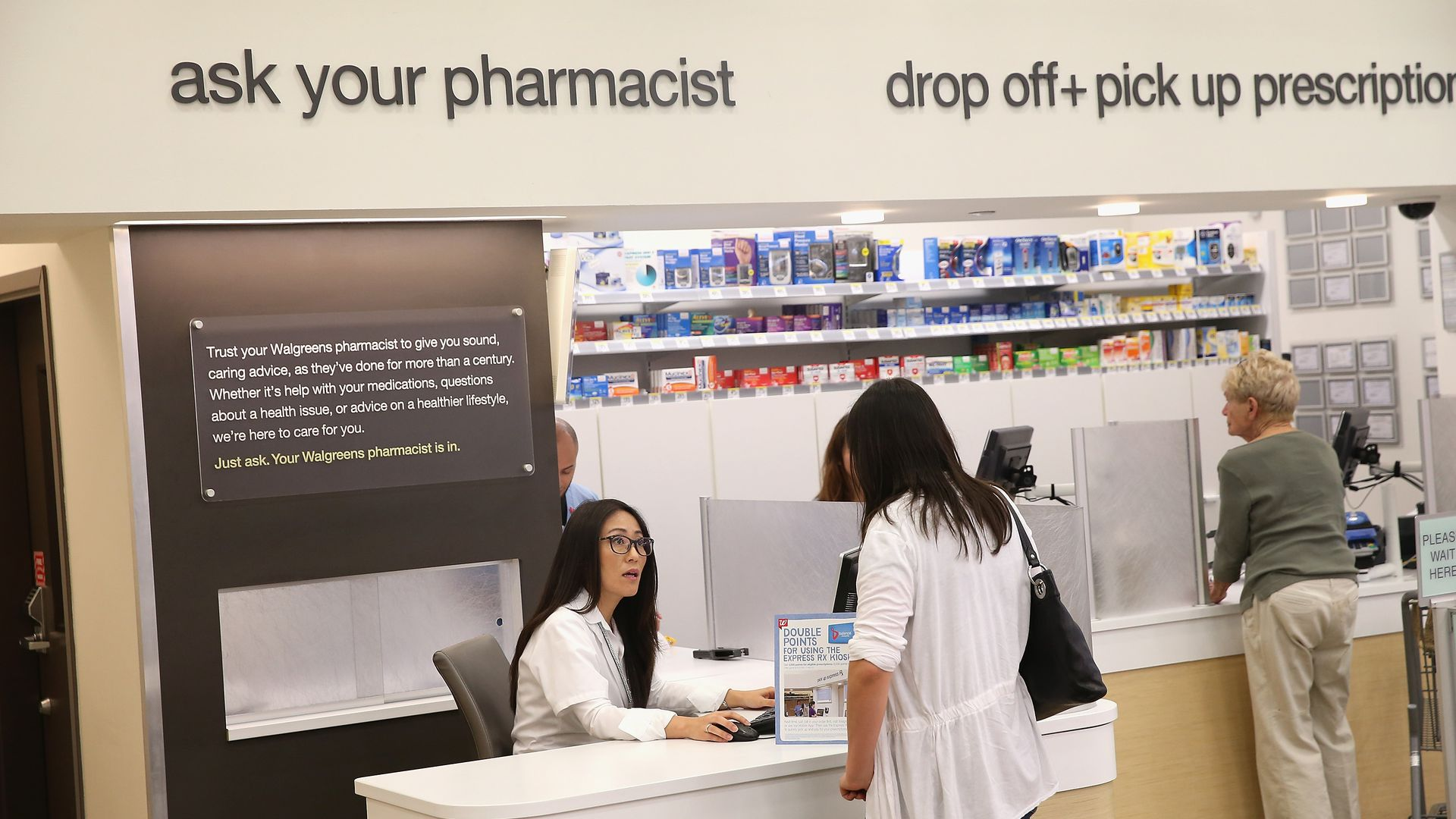 A pharmacists talks to a customer, who is standing in front of a counter.