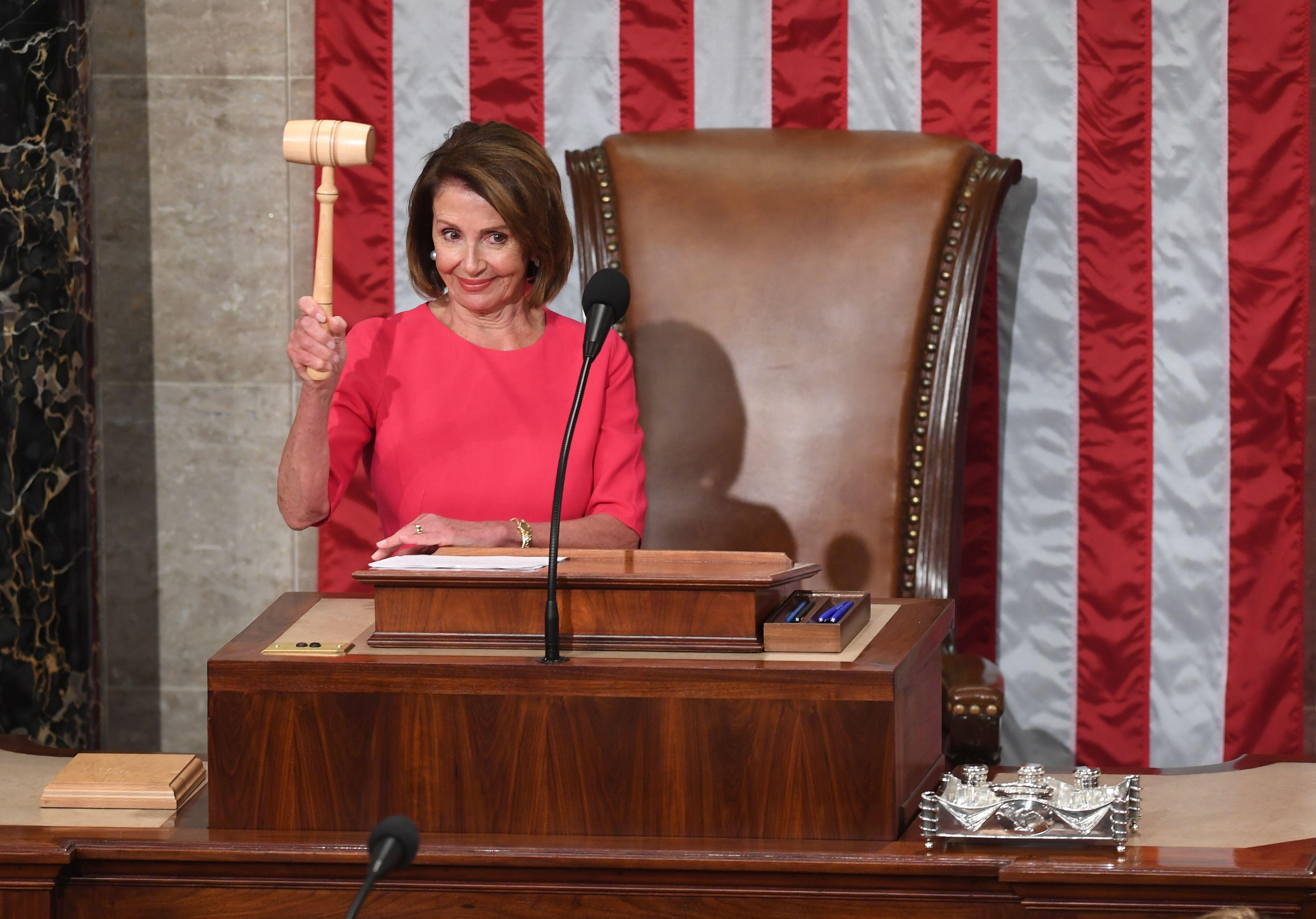 Nancy Pelosi holds gavel smiling.