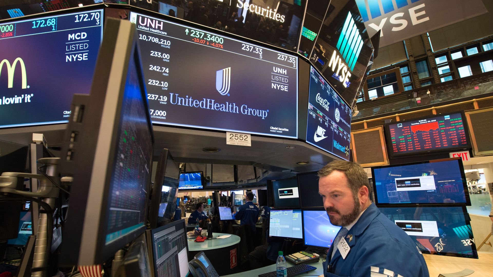 UnitedHealth Group's logo appears on a TV screen on a Wall Street trading floor with a broker standing underneath.