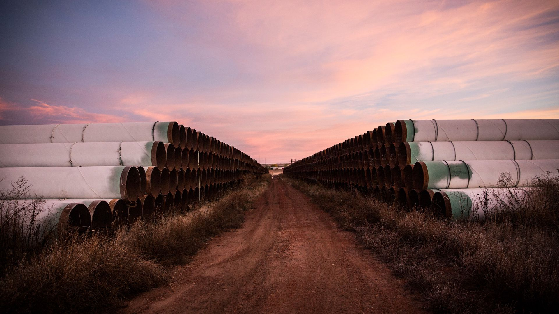 In this image, large pipes are stacked on either side of a dirt road.