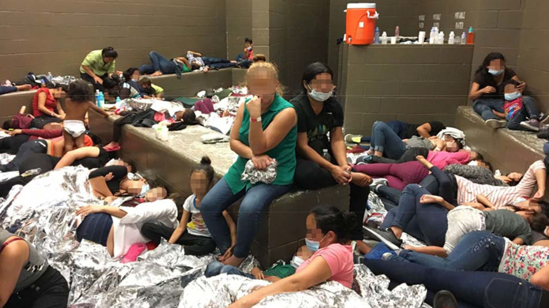 Women and child migrants crammed into a detention cell with aluminum blankets and blurred out faces.
