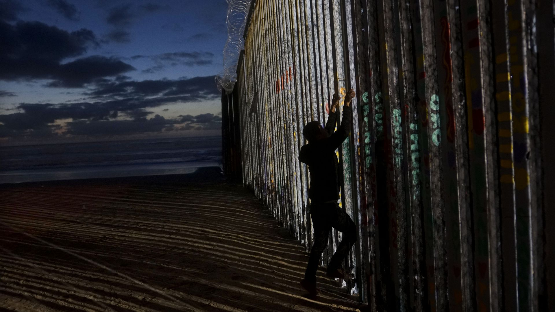 Man climbs border wall in Tijuana.