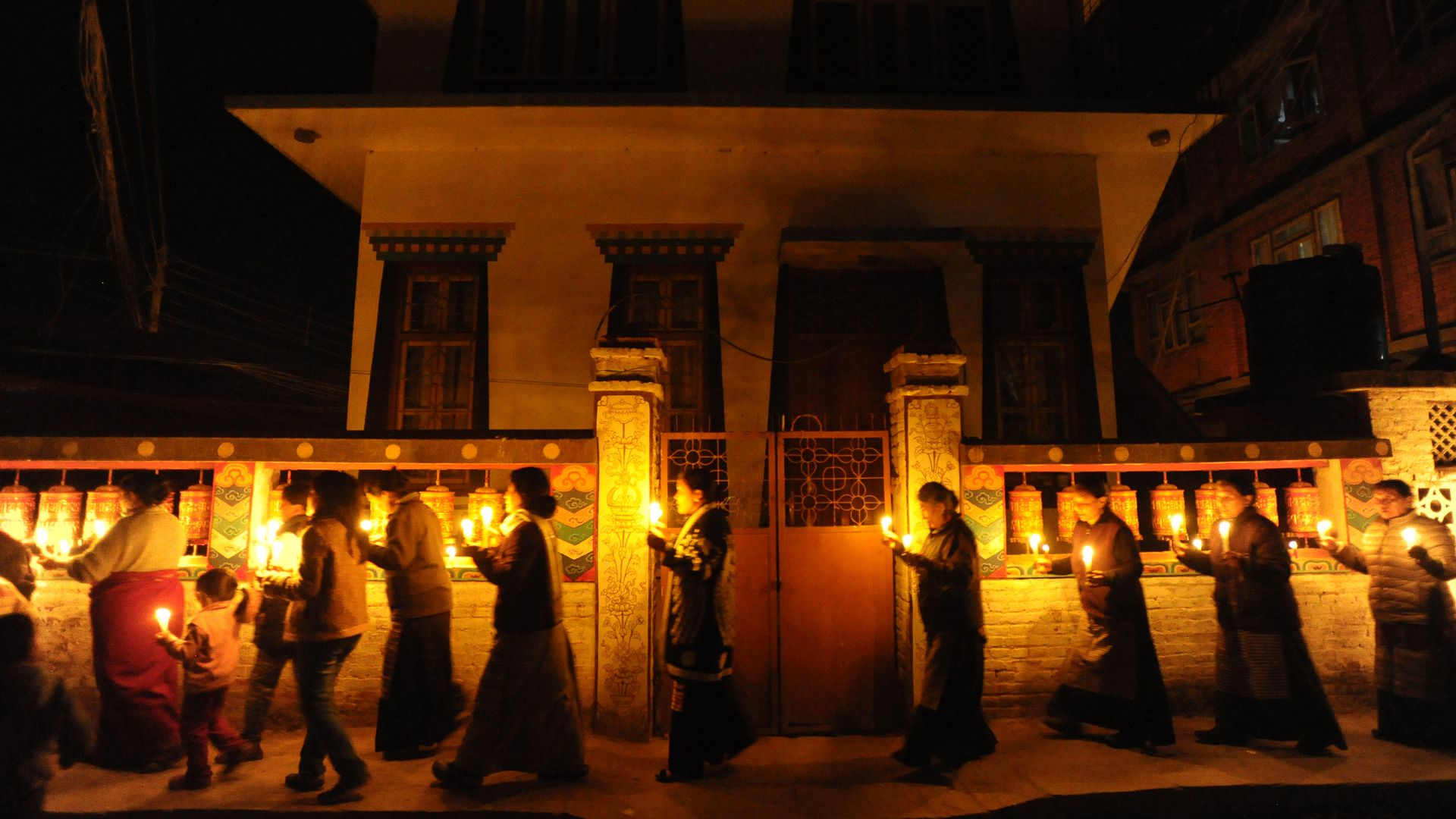 People walk around a temple with candles