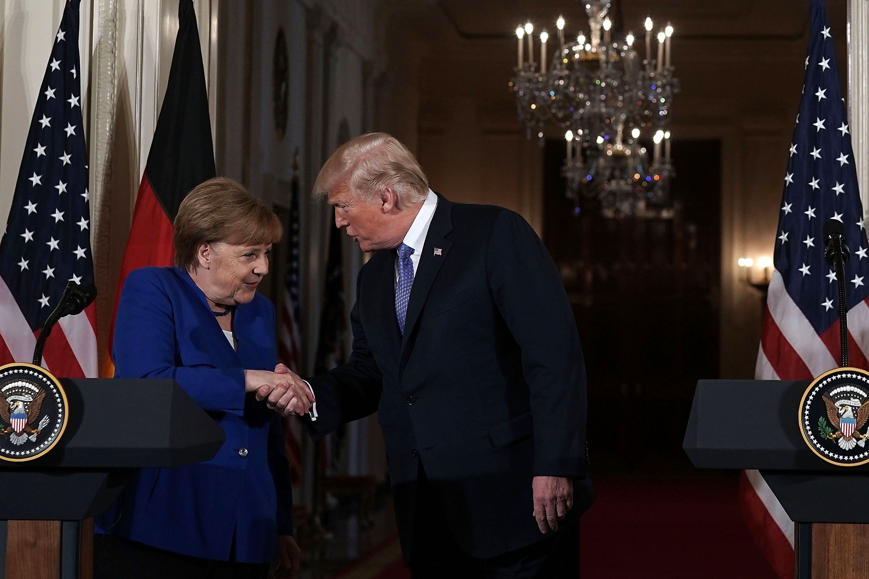 Trump and Merkel handshake.