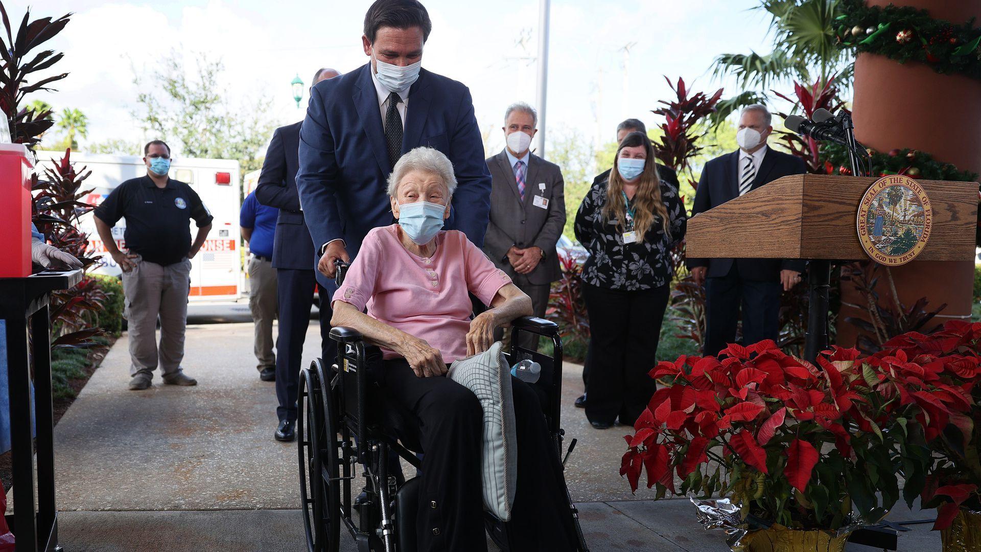 Florida Gov. Ron DeSantis pushes a woman in a wheelchair