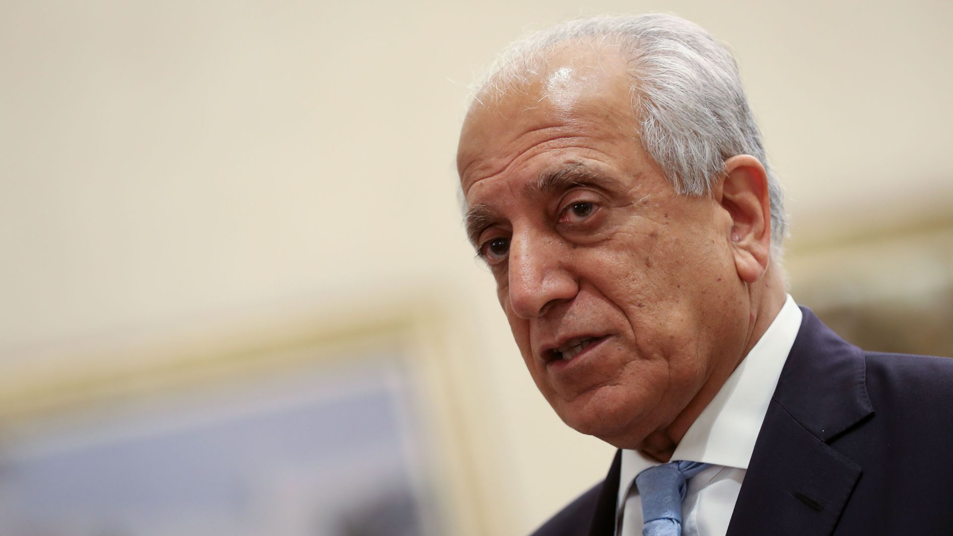 In this image, Khalilzad stands in a suit and tie
