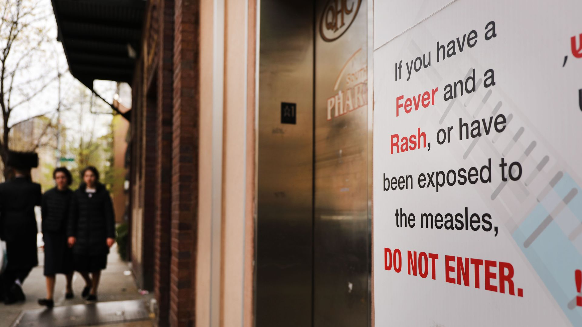 "In this image, a sign posted next to an elevator reads: ""If you have a fever and a rash, or have been exposed to the measles, do not enter.'"