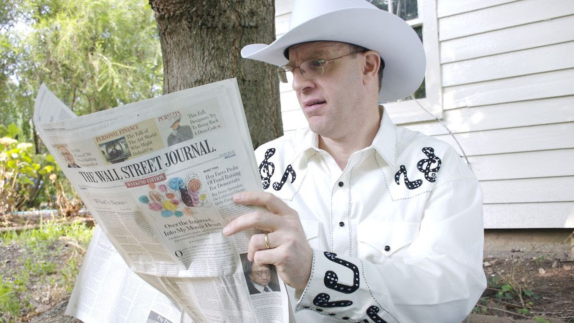Merle Hazard reading a newspaper