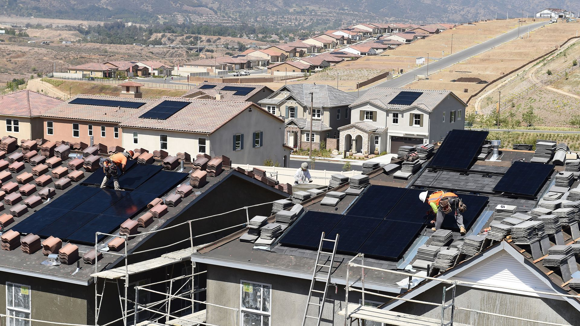 Workers install solar panels on the roofs of homes under construction south of Corona Thursday morning May 3, 2018.