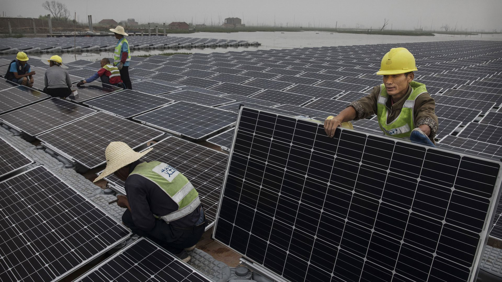 Chinese workers prepare panels that will be part of a large floating solar farm project under construction