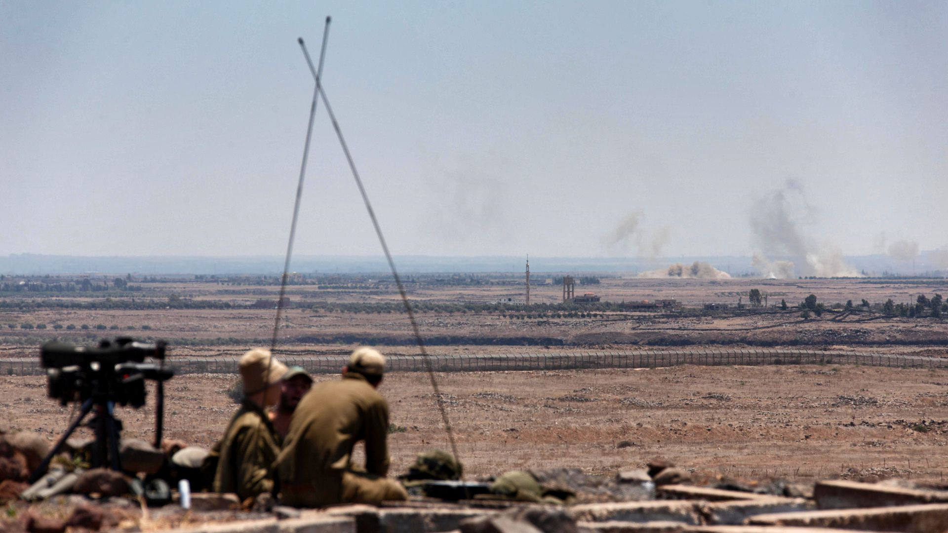 Israeli soldiers in the Golan Heights watch explosions from Syrian fighting