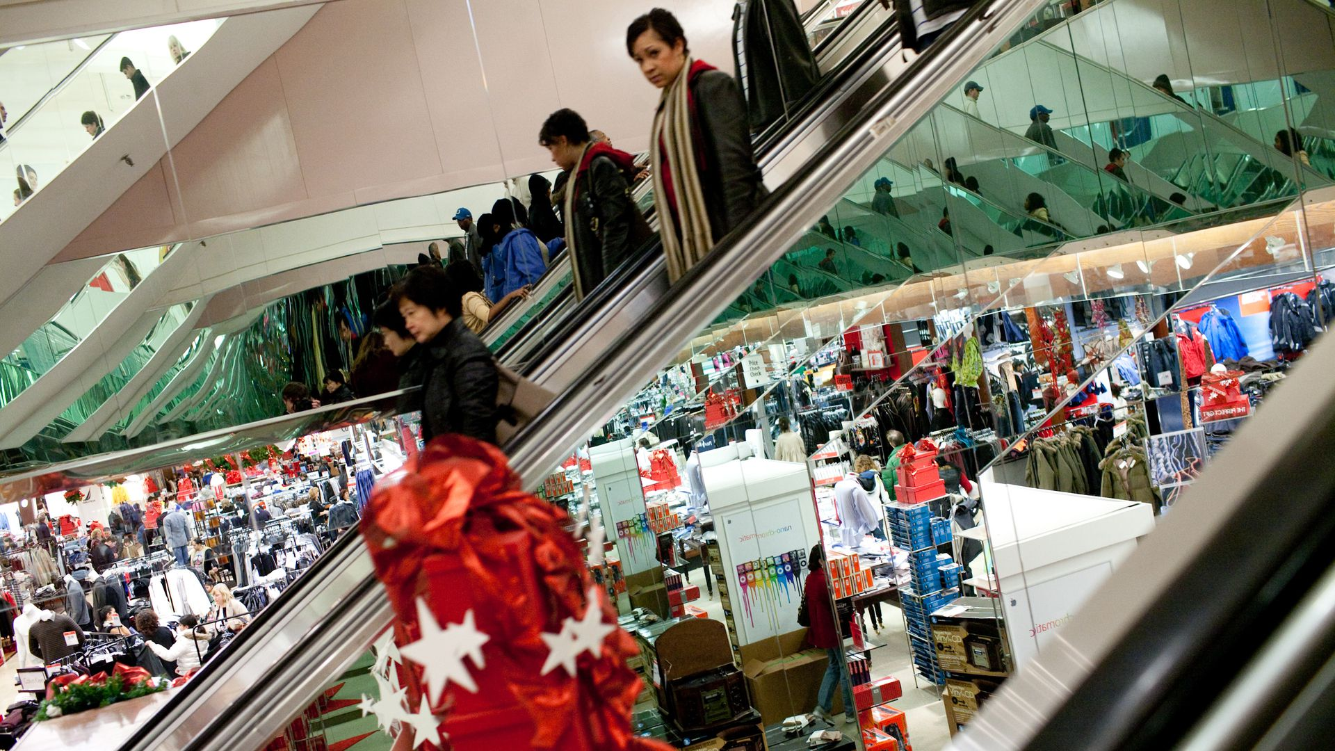 Last-minute shoppers are reflected in the side of an escalator in a Macy's department store at Tysons Corner Center, a mall in suburban Washington, on Christmas Eve on December 24, 2008