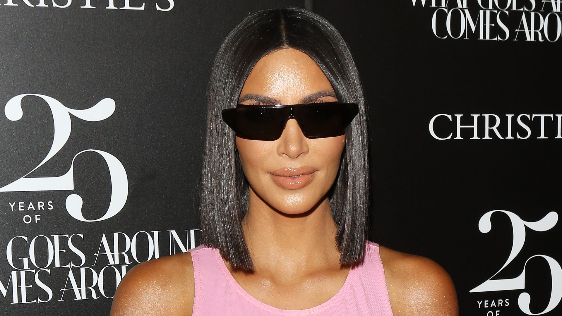 Kim Kardashian where rectangular, dark sunglasses and a light pink tank top posing for a photo seemingly on a red carpet