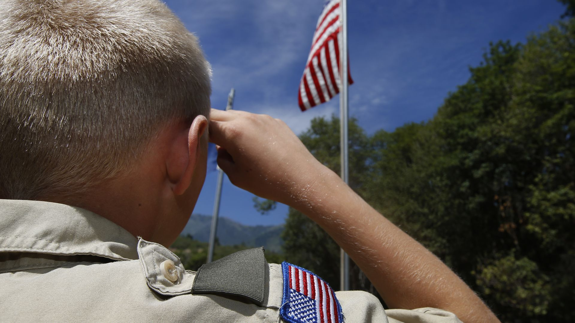 A Boy Scout salutes the American flag at camp Maple Dell.