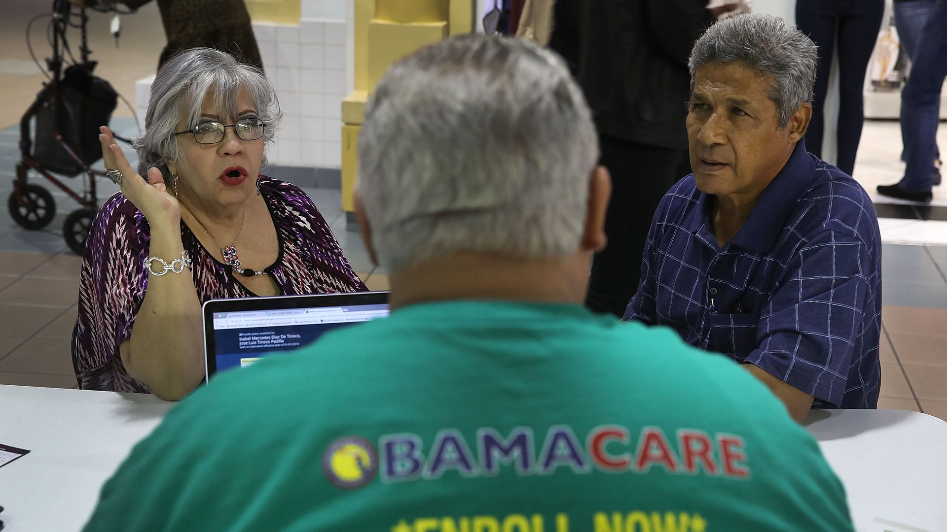 A man helps two Florida residents sign up for insurance under Obamacare