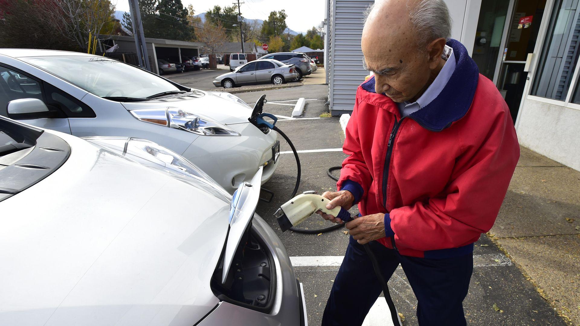 Man charging an electric car in public