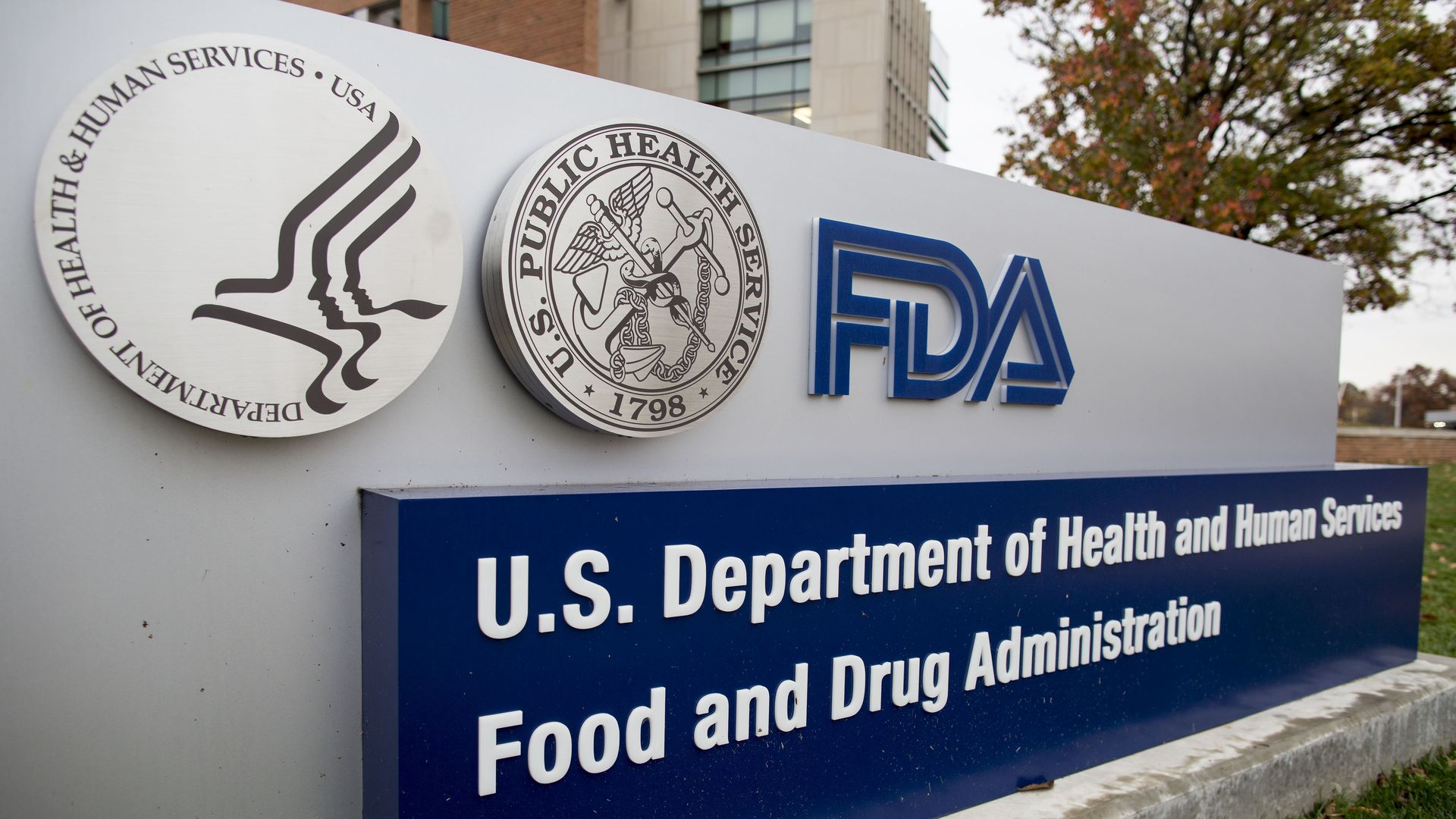 In this image, a sign displays the FDA and HHS logos