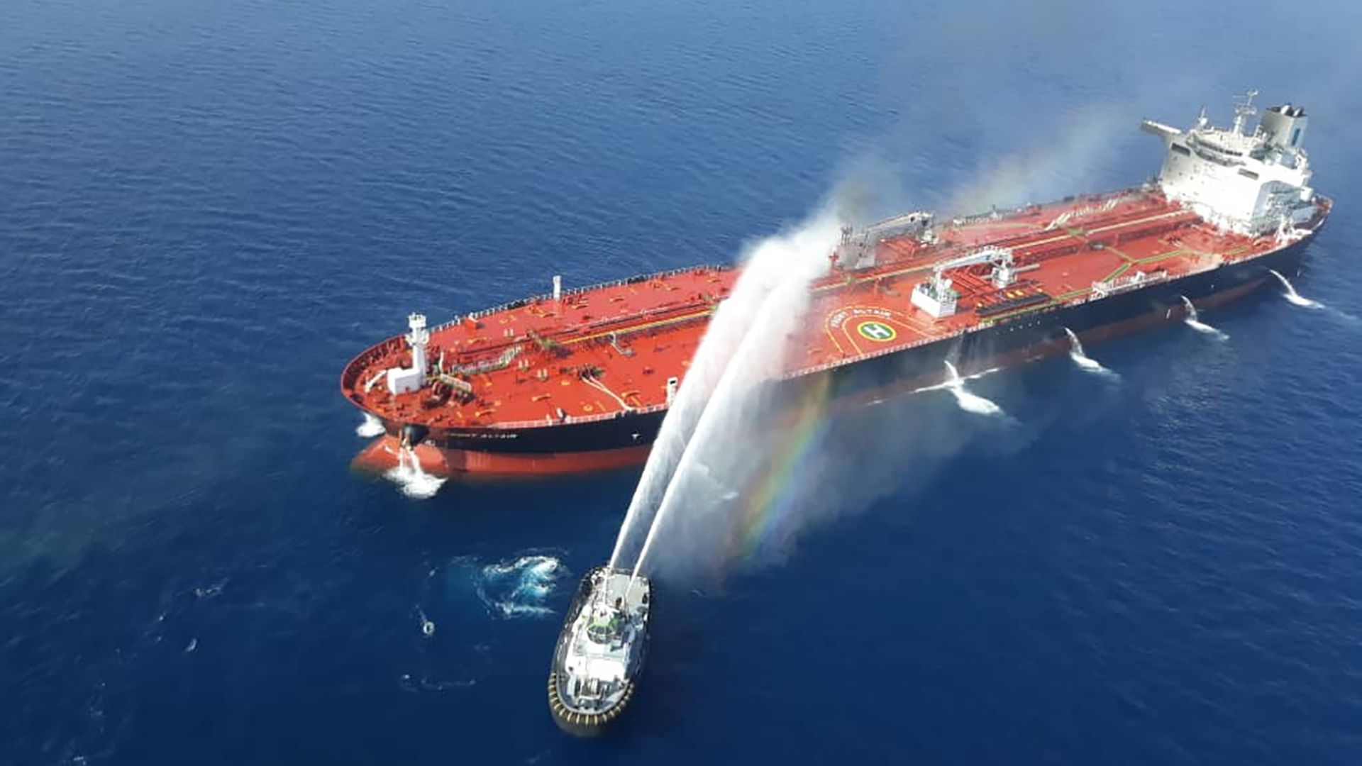 This image is a birds eye view of an oil tanker being sprayed with water from a smaller boat.