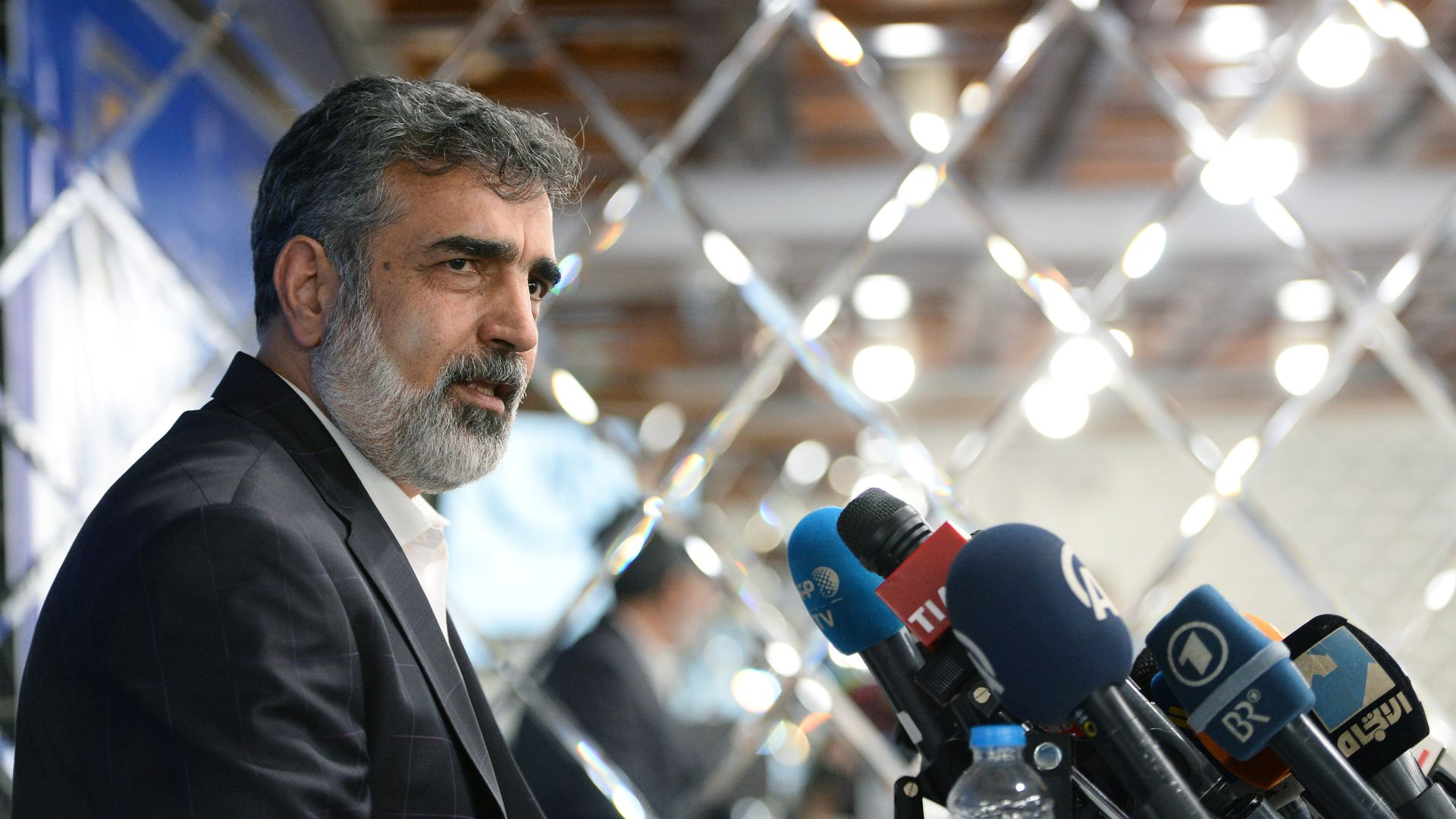 spokesman for Iran's atomic energy agency in front of microphones at a press conference