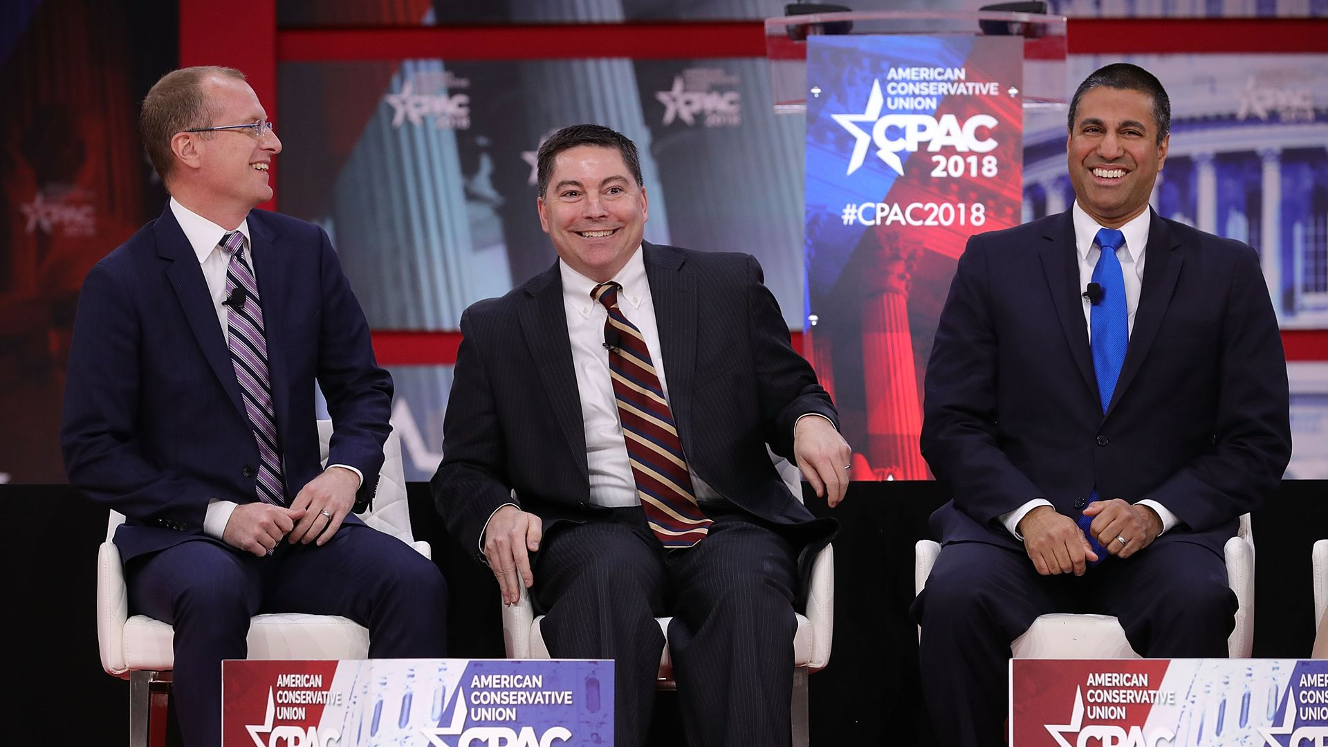 Three FCC commissioners laughing on a stage