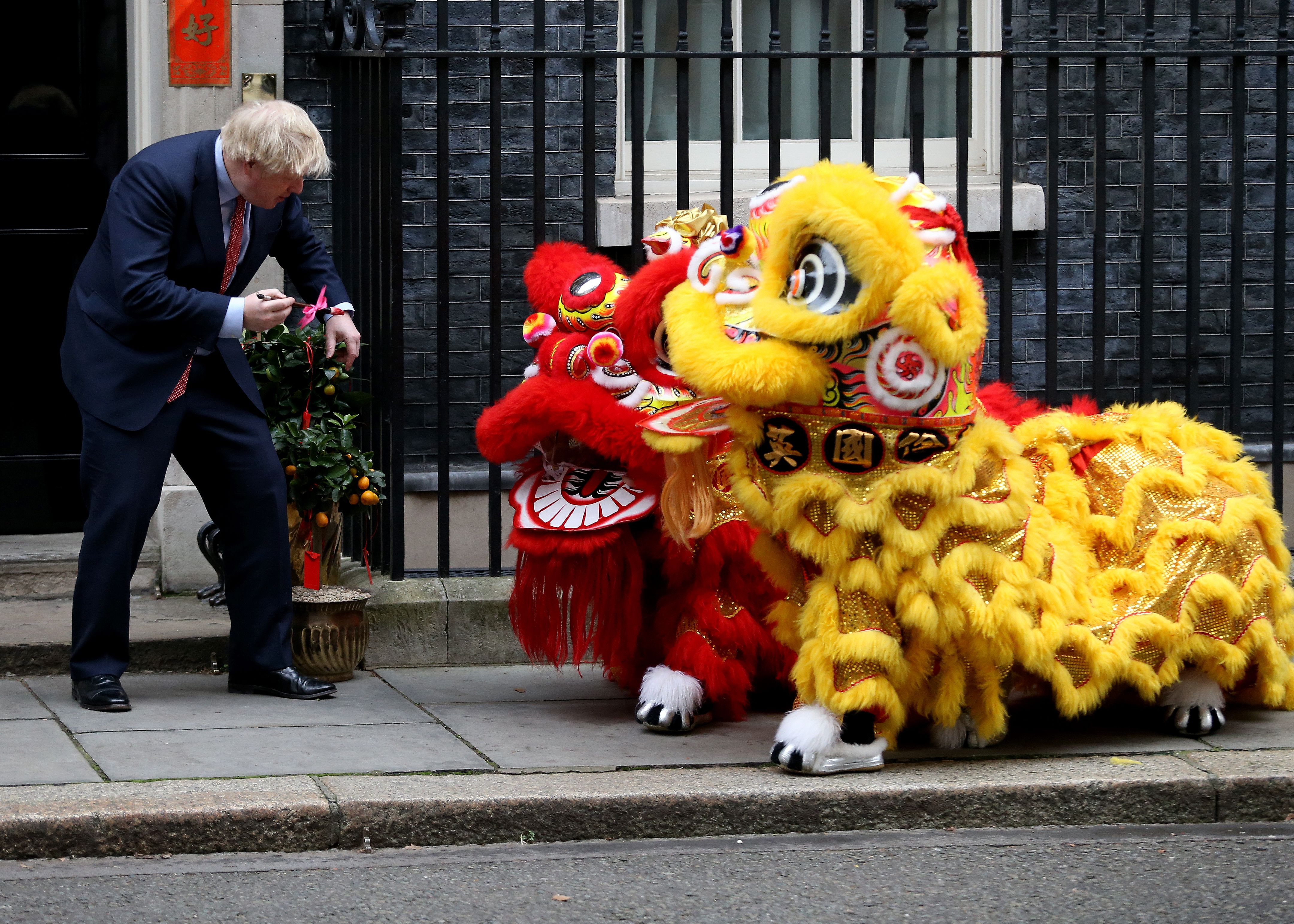 In this image, Boris Johnson greets two lions for Lunar New Year