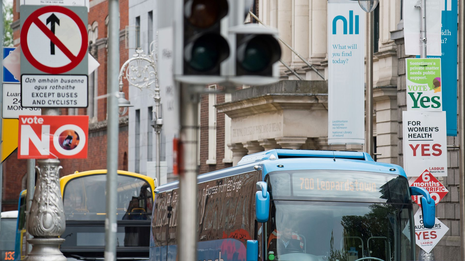 Buses pass posts covered in signs for anti- and pro-repeal of Ireland's abortion ban.