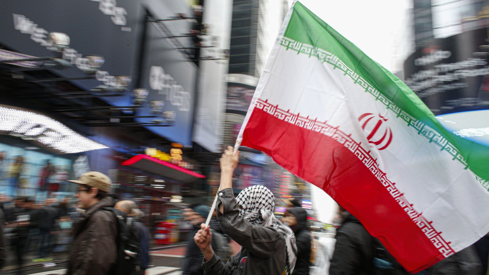 In this image, a person holds the Iranian flag