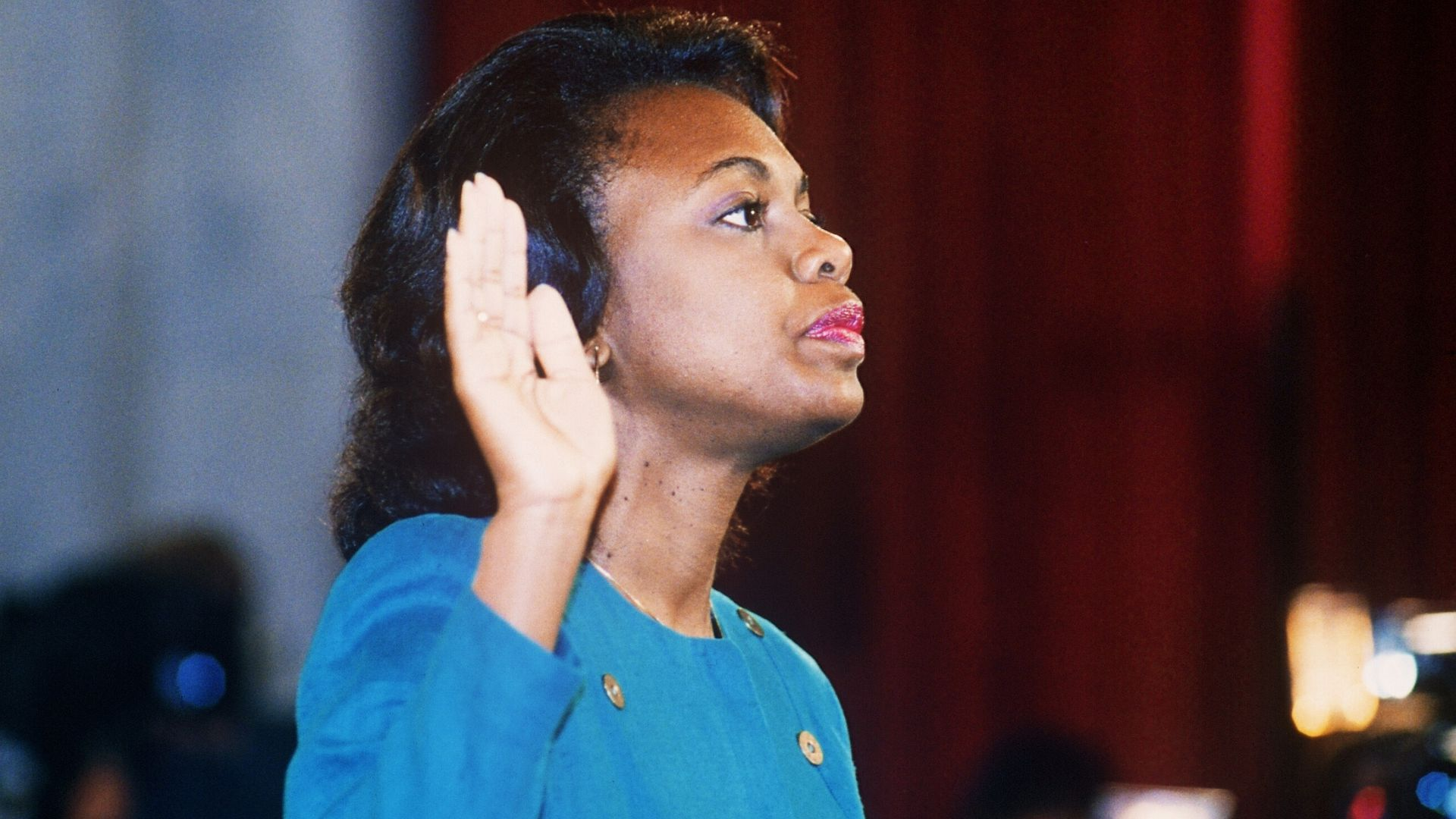 An old photo of Anita Hill testifying in front of the Senate in a bright blue suit