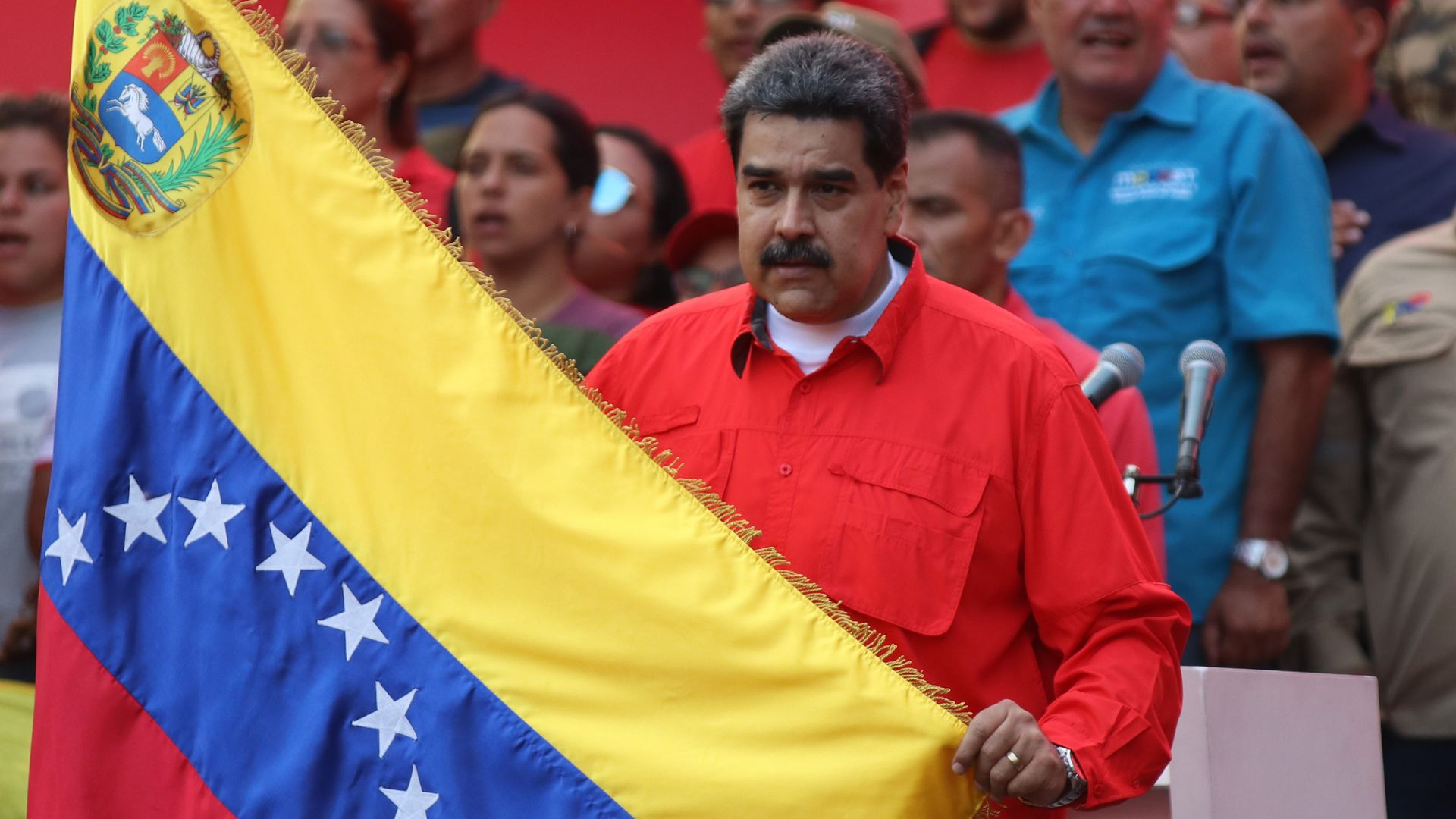 Nicolas Maduro holding up the Venzuelan flag at a rally