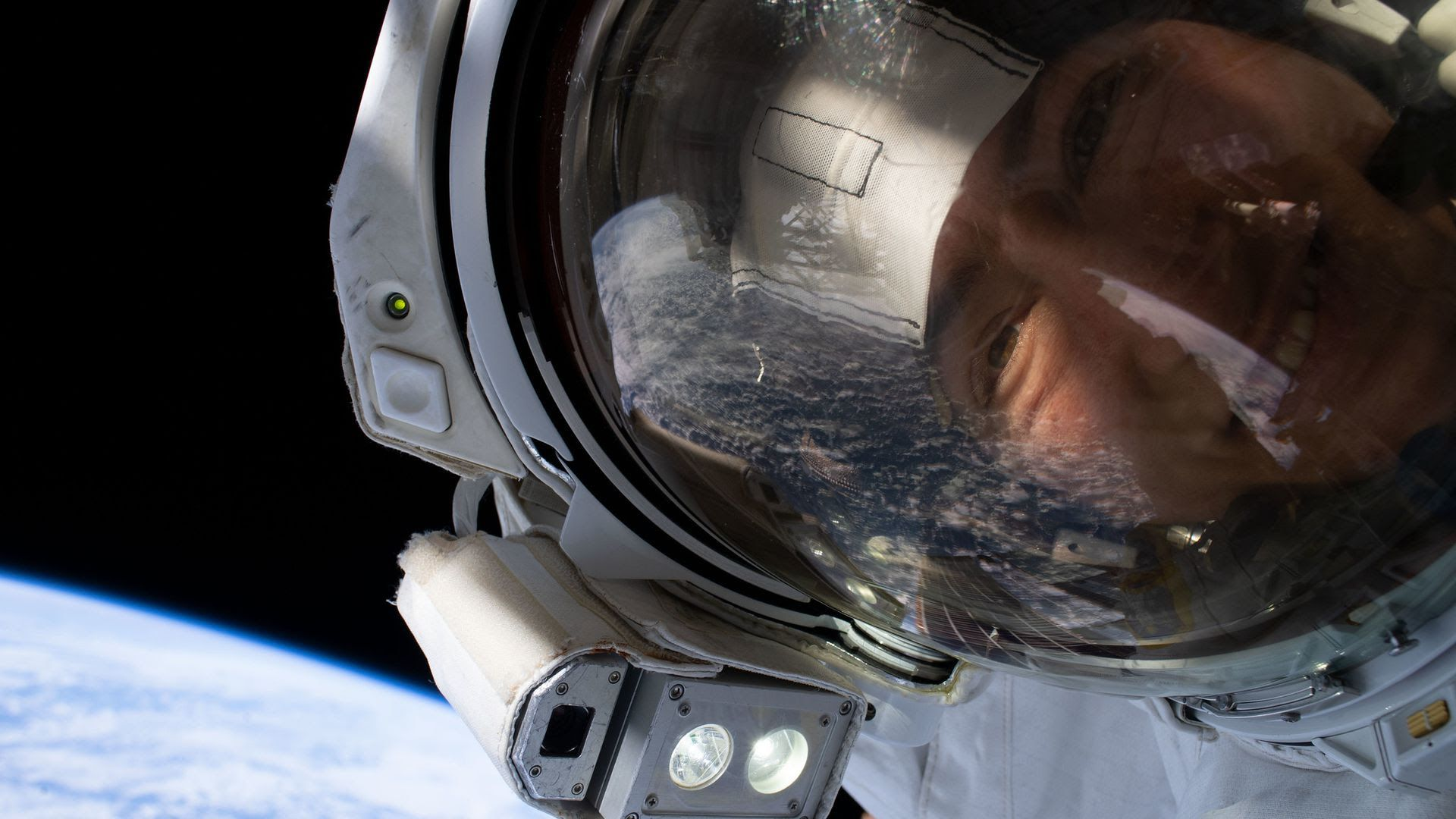 A female astronaut takes a selfie in outer space.