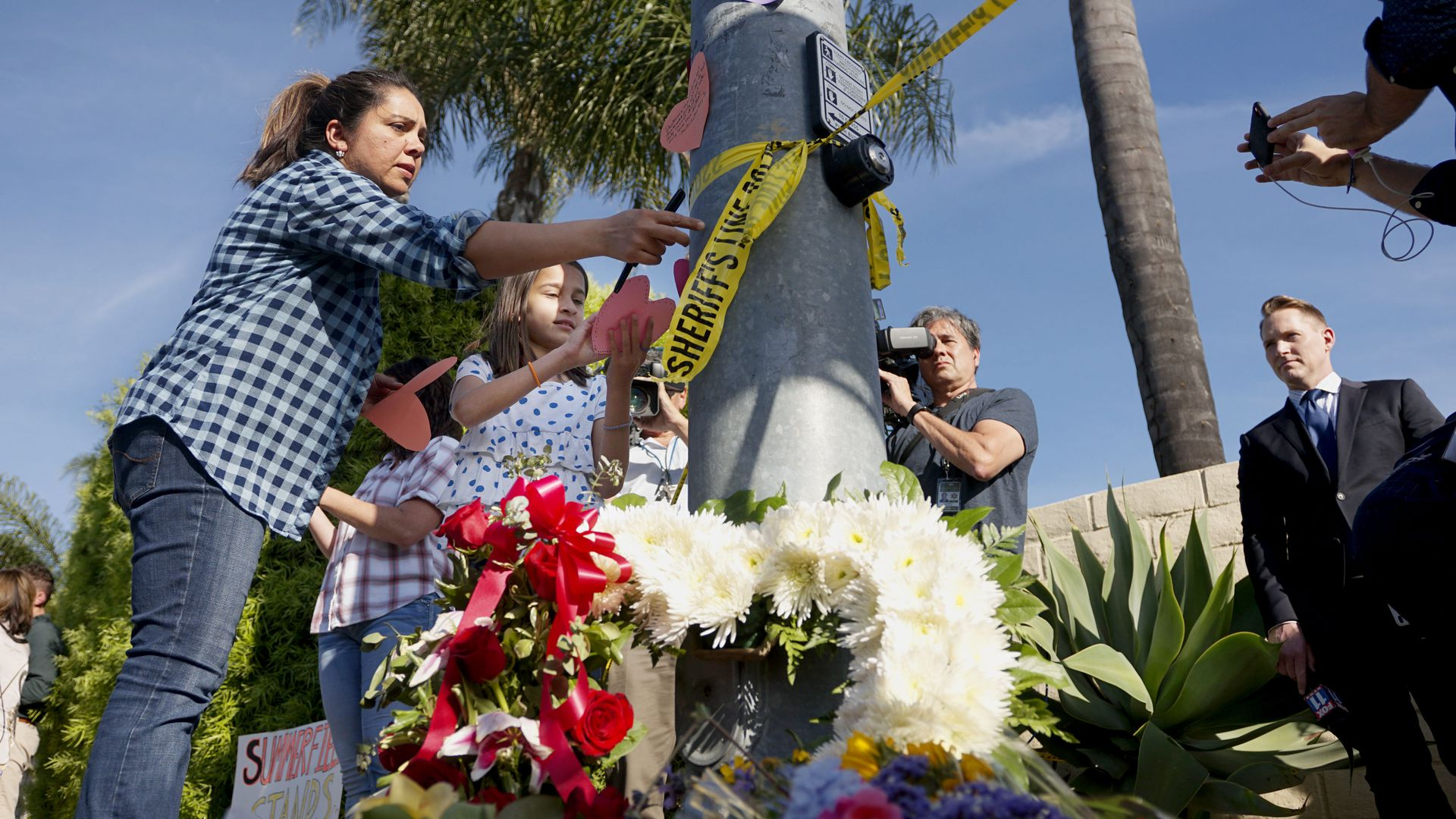 A woman and a young girl place notes on a light post near flowers across the street from the Chabad of Poway Synagogue after a shooting in Poway, California, Saturday.