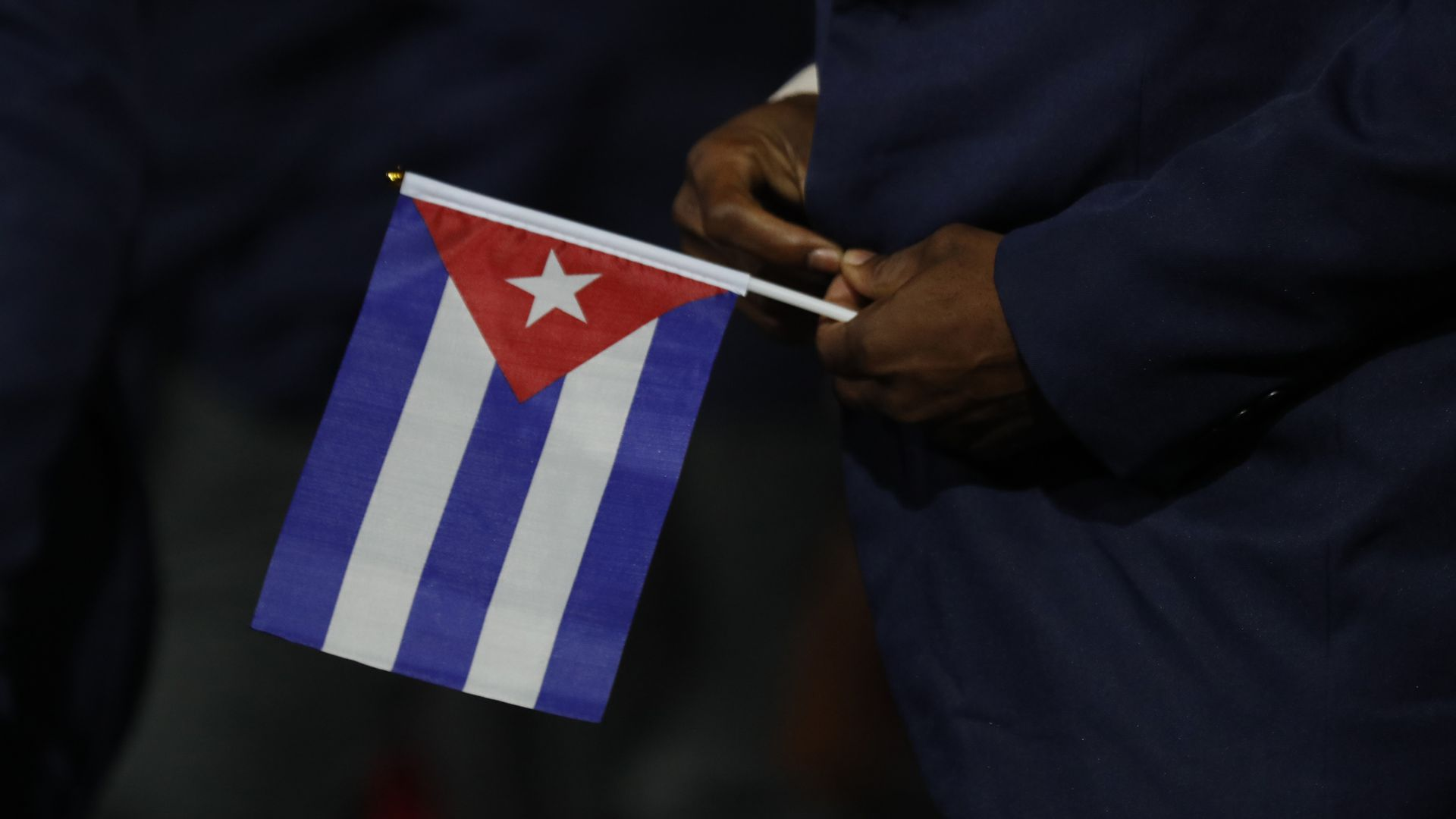 In this image, a man holds a small Cuban flag