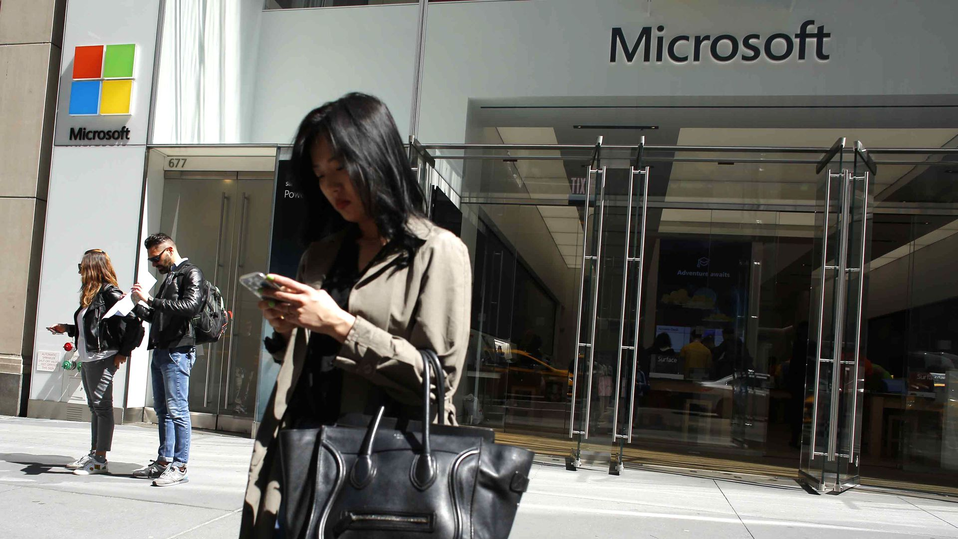 A photo of a woman on her phone outside a Microsoft office