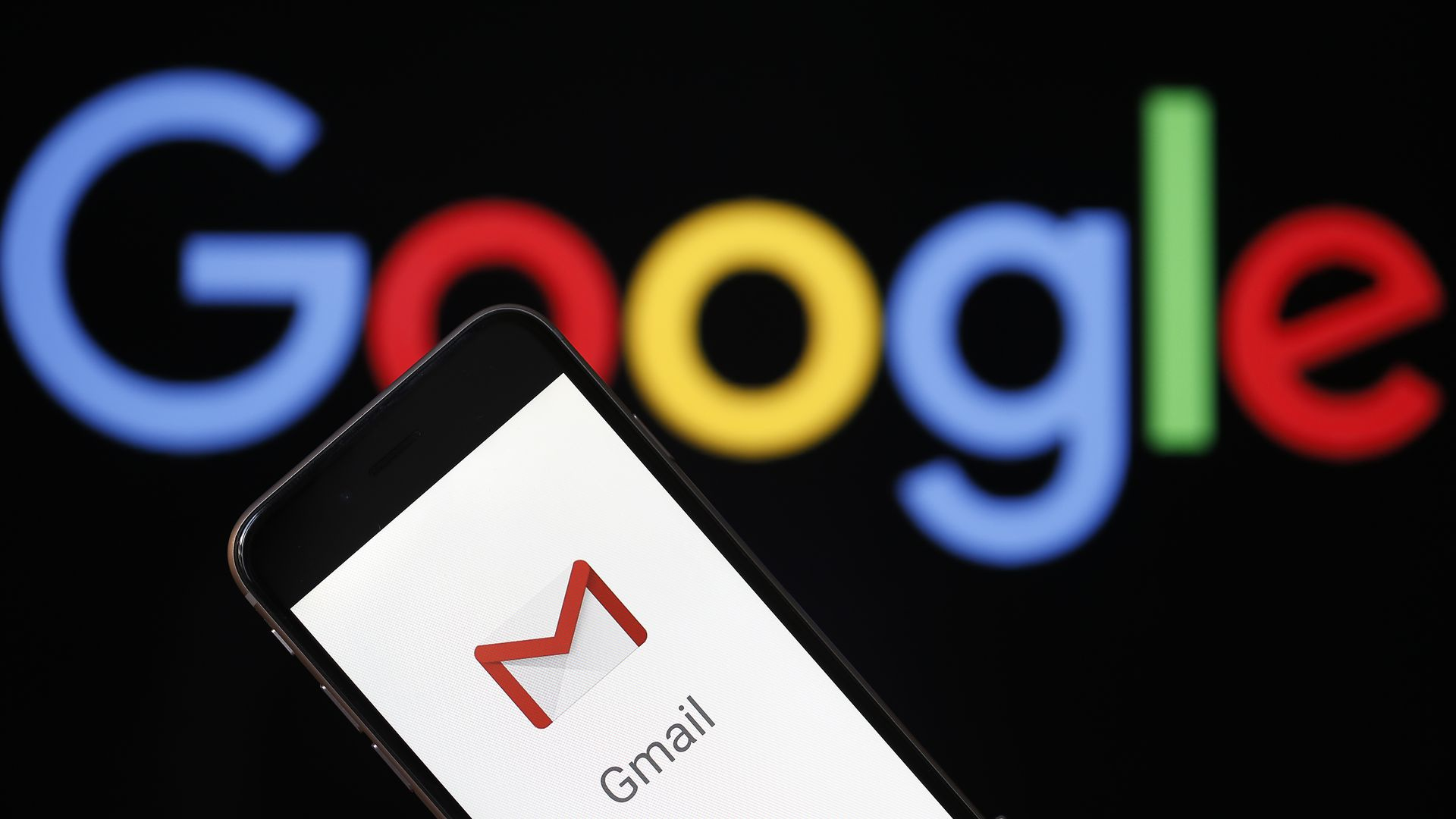 In this image, a phone screen with the Gmail logo is held in front of a large Google logo.
