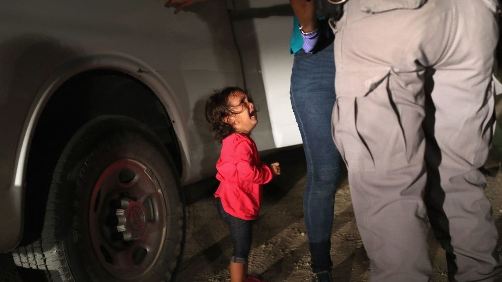 A girl crying as her mother is searched by a border patrol agent