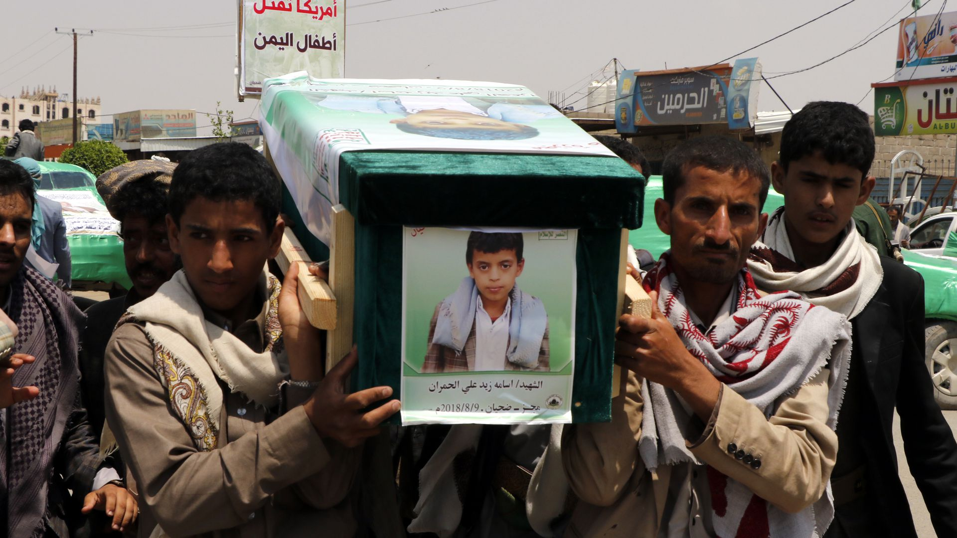 Men carry a coffin with the picture of a child on the front of it.