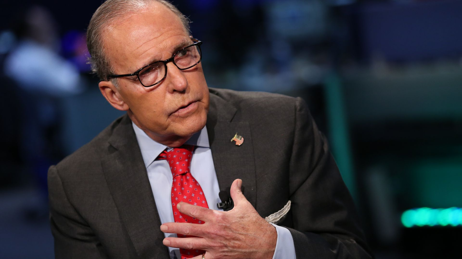 Larry Kudlow wearing a suit with red tie.