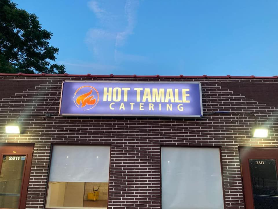 Hot Tamale Catering on a purple sign in front of the restaurant's storefront in Des Moines.