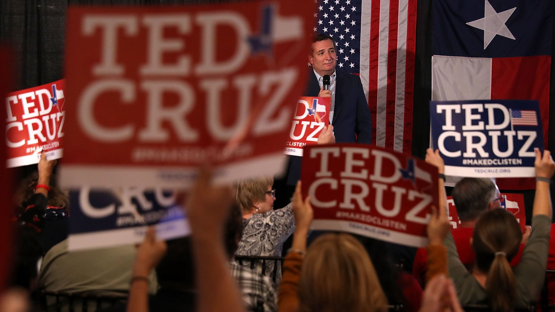 Ted Cruz standing on stage at a rally in Texas, with a bunch of people holding Ted Cruz signs
