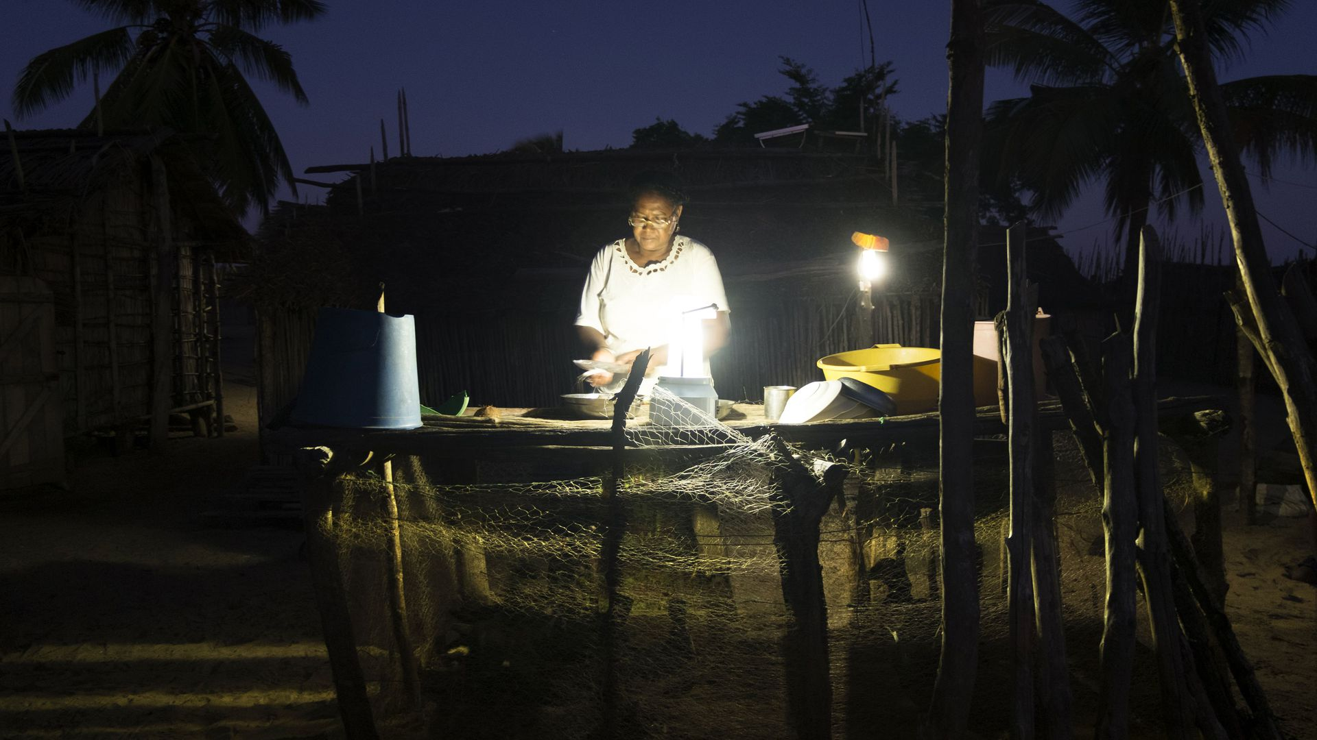 A woman in Madagascar working outside at night in lamplight