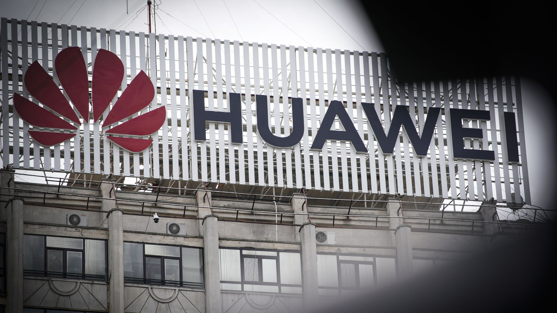 In this image, the Huawek logo is seen on the side of a building on a foggy day.