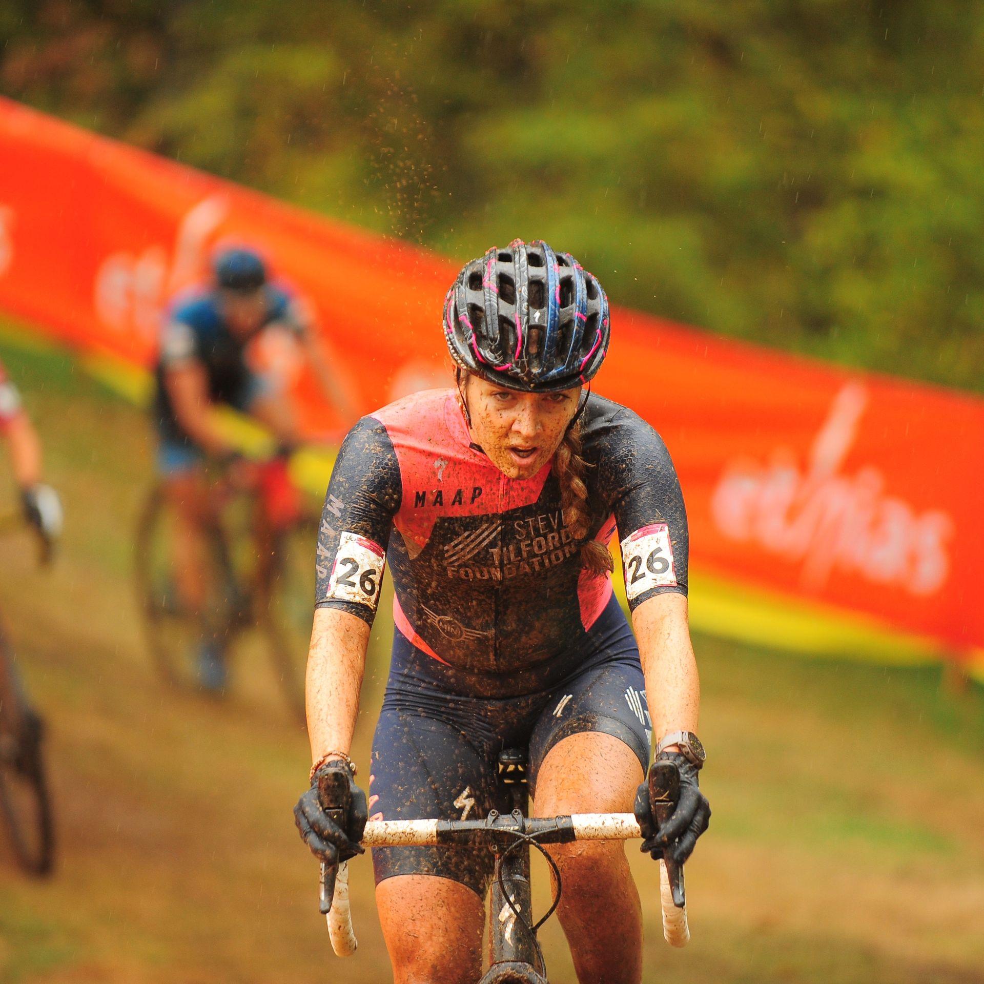 Determined woman racing a bike in the rain.