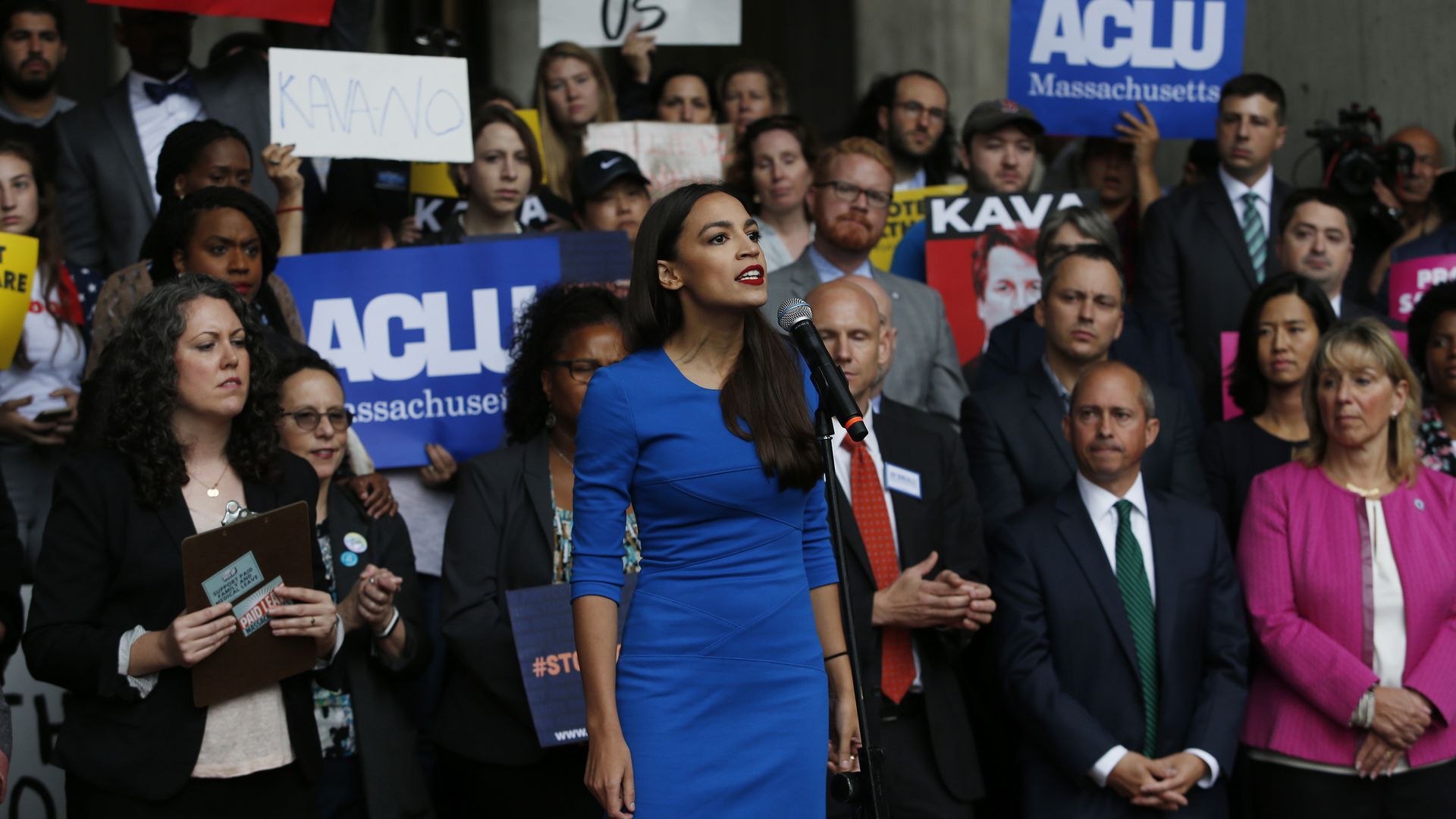 Alexandria Ocasio-Cortez stands before protestors while addressing a rally in Boston