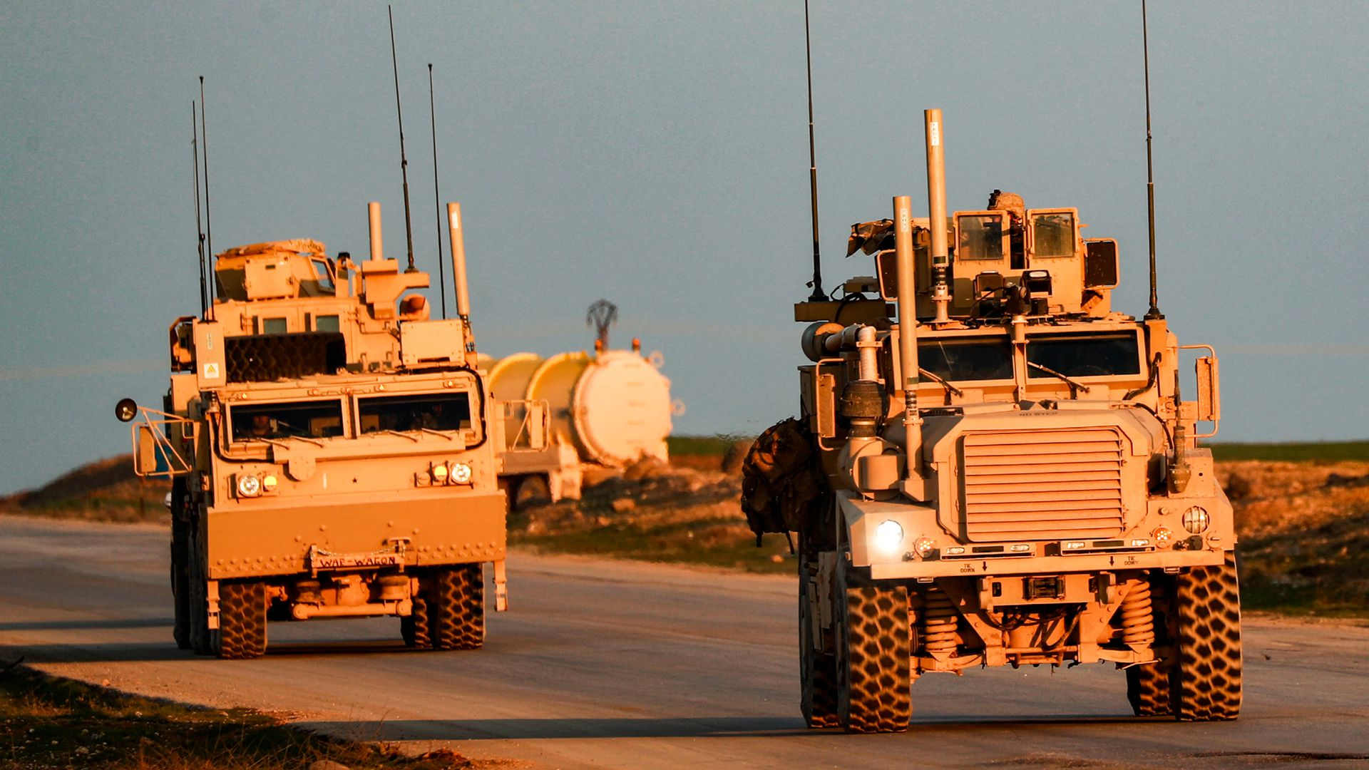 Marine Corps tactical vehicles drive along a road in Syria