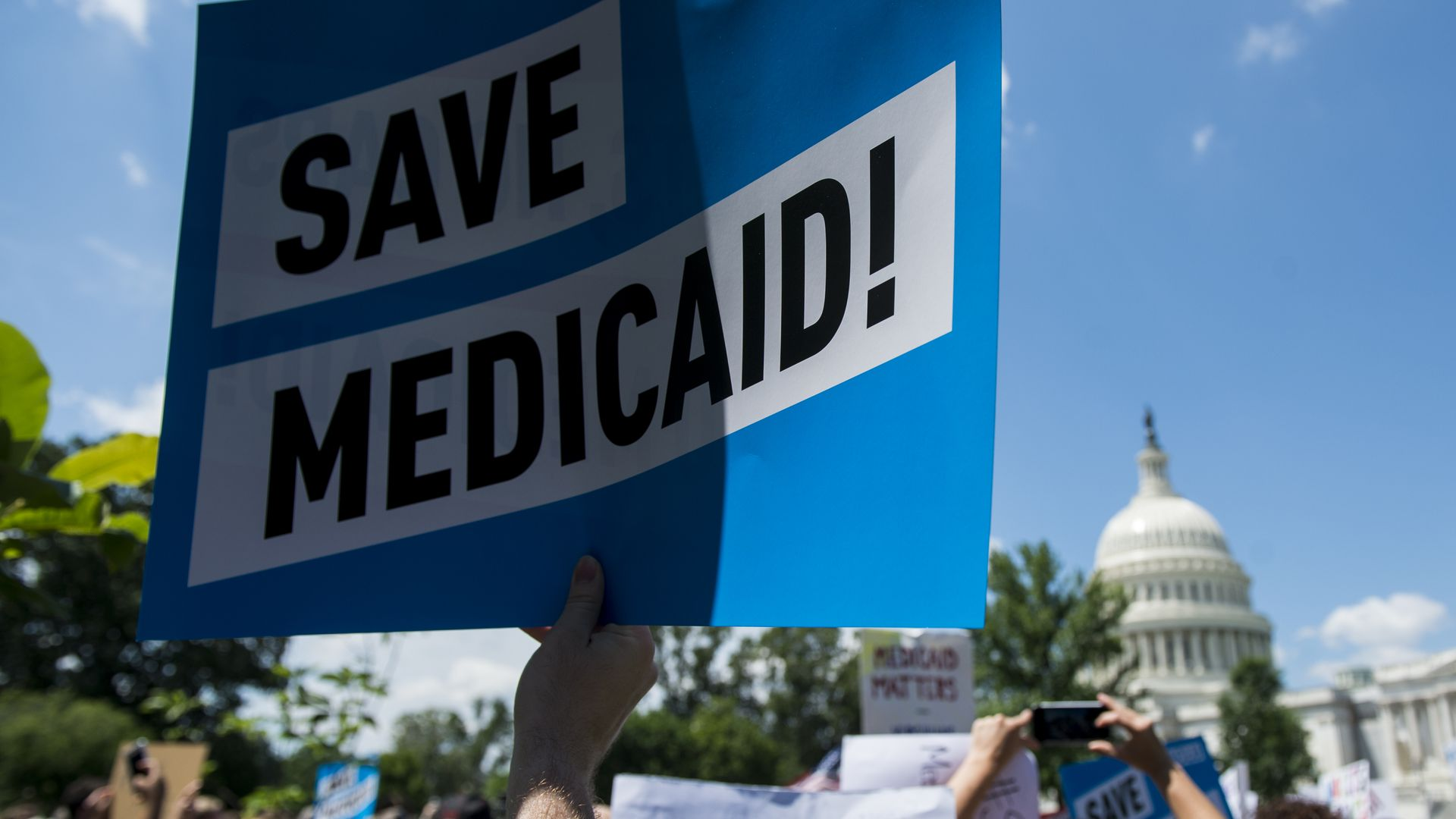 "A person holds up a sign that says ""Save Medicaid!"""